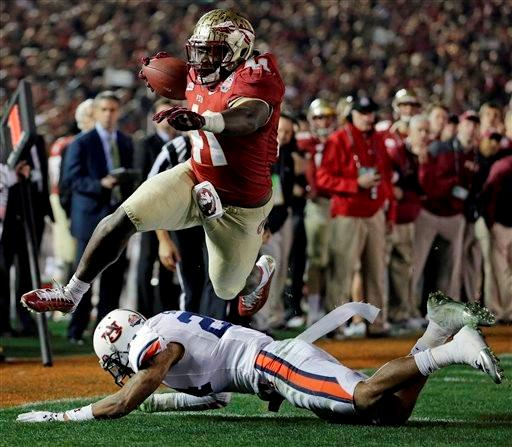 Florida State's Chad Abram leaps over Auburn's Ryan Smith for a touchdown during the second half of the NCAA BCS National Championship college football game Monday, Jan. 6, 2014, in Pasadena, Calif.