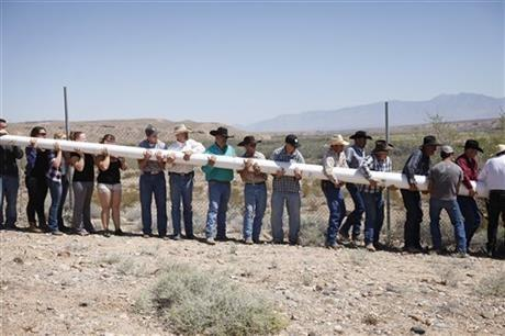People help erect a pole to hang a banner during a rally in support of Cliven Bundy near Bunkerville Nev. Monday, April 7, 2014, 2014.