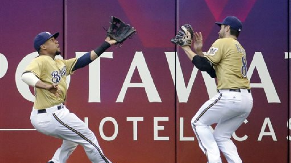 Milwaukee Brewers' Carlos Gomez and Ryan Braun (8) colide going after a ball hit by Philadelphia Phillies' Cameron Rupp during the sixth inning of a baseball game Thursday, July 10, 2014, in Milwaukee. Gomez caught the ball for the out. (AP Photo/Morry Gash)