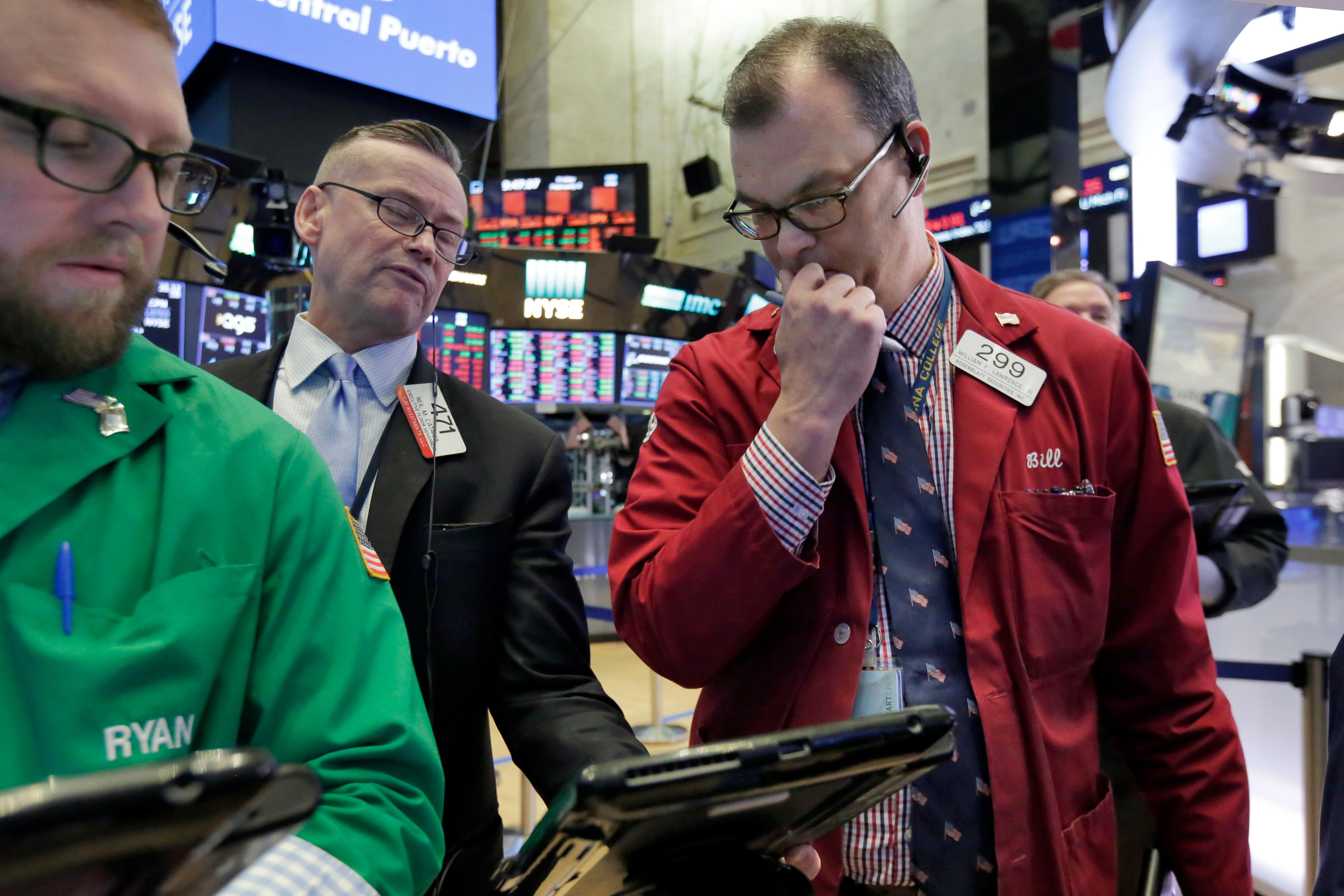Traders Ryan Falvey, left, Neil Catania, center, and William Lawrence work on the floor of the New York Stock Exchange, Friday, Feb. 2, 2018. Technology companies were leading stocks broadly lower in early trading, extending the market's slide into a second day. (AP Photo/Richard Drew)