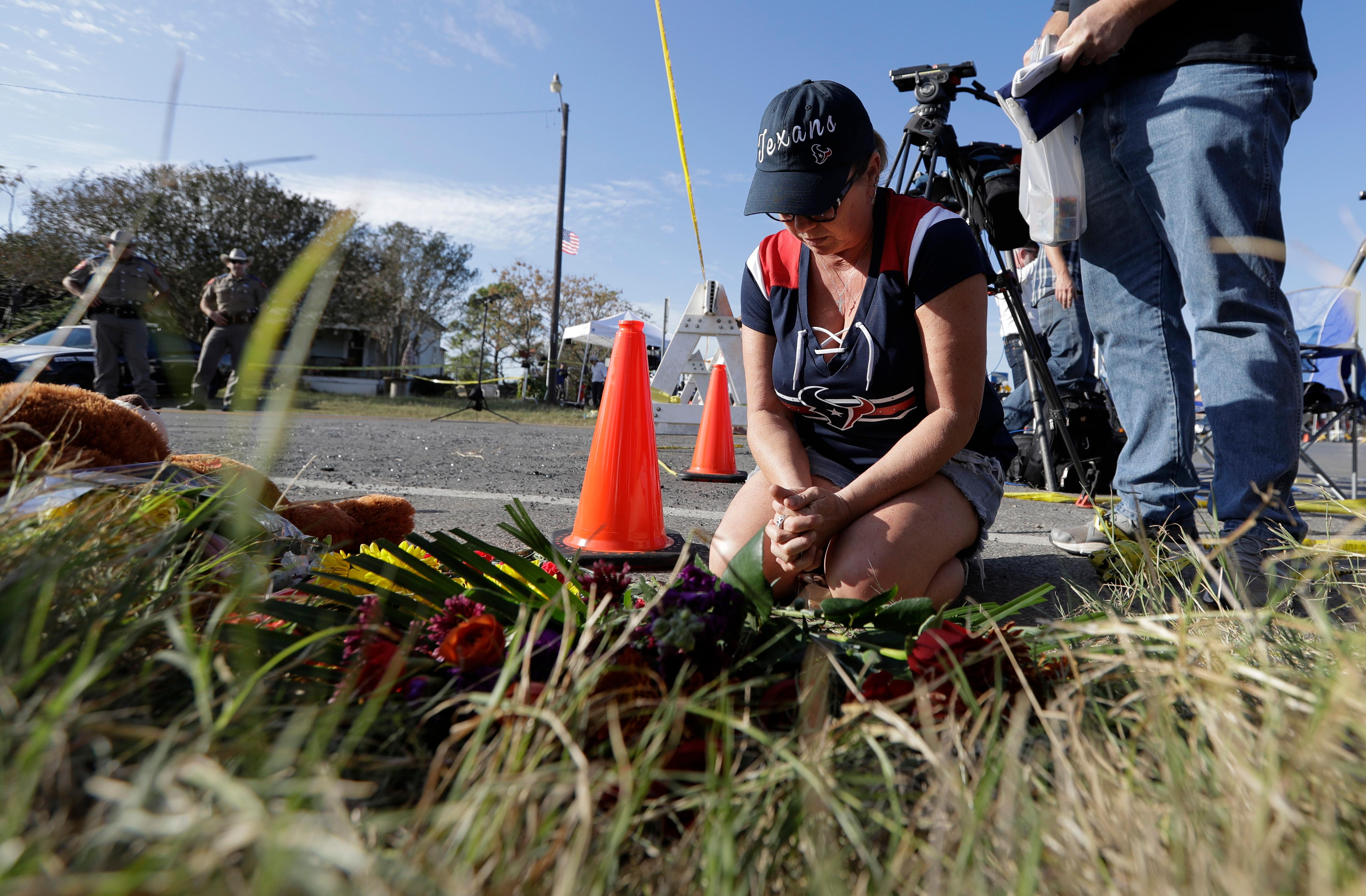 Rebecca Thompson prays at a makeshift memorial near the scene of a shooting at the First Baptist Church of Sutherland Springs to honor victims, Monday, Nov. 6, 2017, in Sutherland Springs, Texas. A man opened fire inside the church in the small South Texas community on Sunday, killing and wounding many. (AP Photo/Eric Gay)