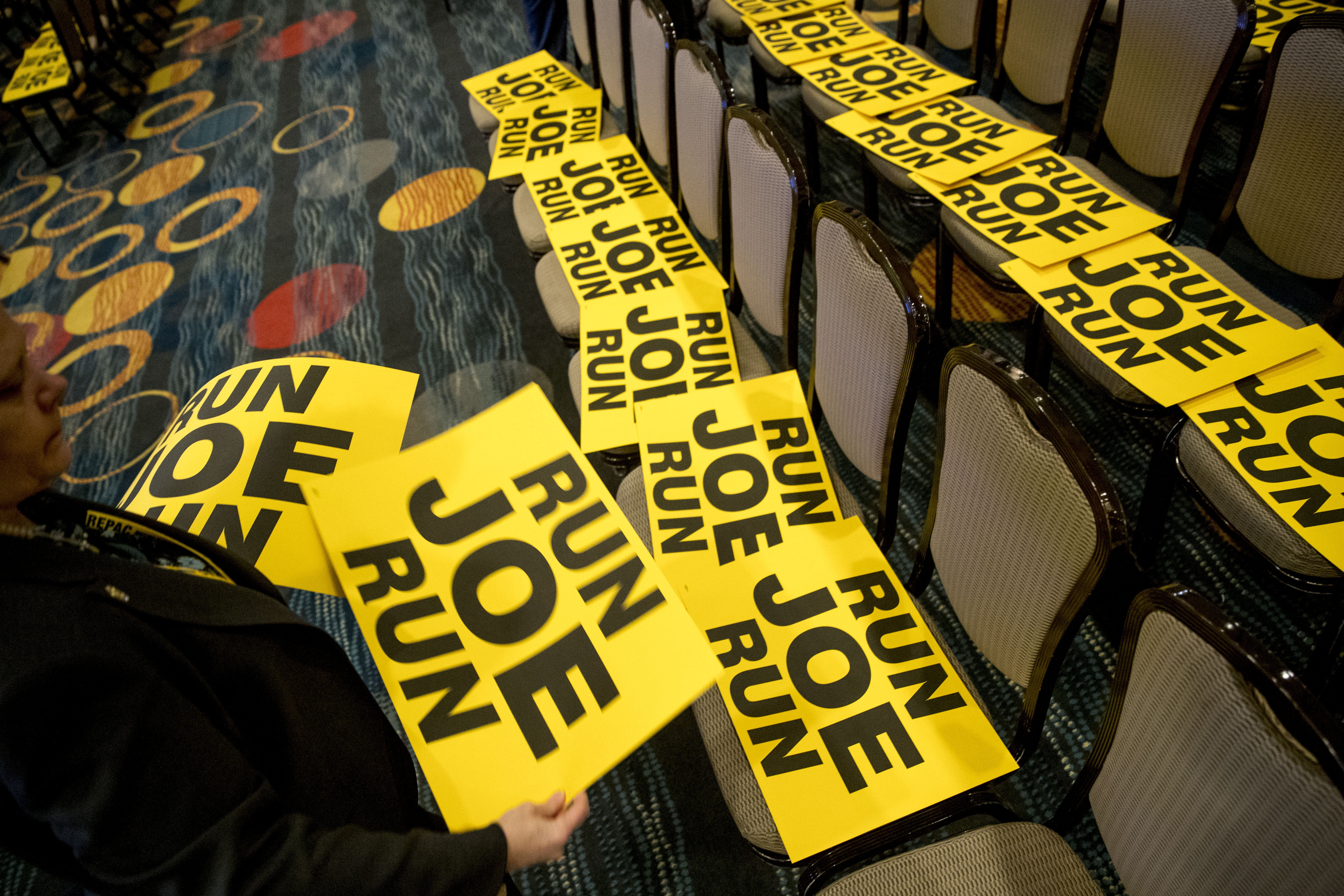 "Workers lay out signs that read ""Run Joe Run"" ahead of a speech by former Vice President Joe Biden to the International Association of Firefighters at the Hyatt Regency on Capitol Hill in Washington, Tuesday, March 12, 2019. (AP Photo/Andrew Harnik)"