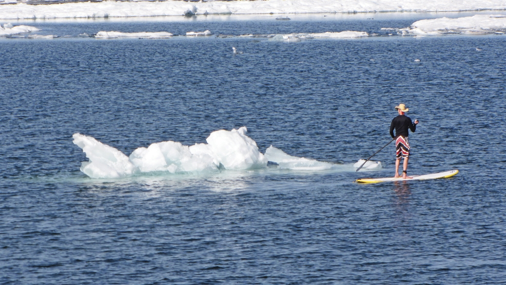 In this photo taken on Tuesday, May 27, 2014, a paddle boarder moves past a large piece of ice in Lake Superior in Marquette, Mich. The warmest temperatures of the year sent people to the Lake Superior shoreline, where small icebergs were abundant in the water, the final vestige of a bitterly cold winter. (AP Photo/The Mining Journal, Dave Schneider)