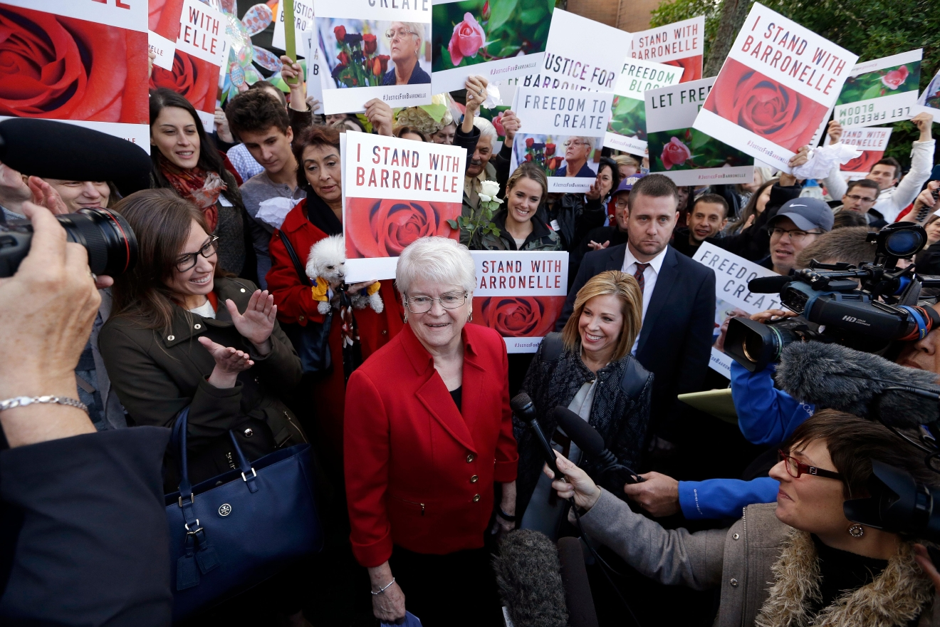 Barronelle Stutzman, center, a Richland, Wash., florist who was fined for denying service to a gay couple in 2013, smiles as she is surrounded by supporters after a hearing before Washington's Supreme Court, Tuesday, Nov. 15, 2016, in Bellevue, Wash. Stutzman was sued for refusing to provide services for a same sex-wedding and says she was exercising her First Amendment rights, but justices questioned whether ruling in her favor would mean other businesses could turn away customers based on racial or other grounds. (AP Photo/Elaine Thompson)