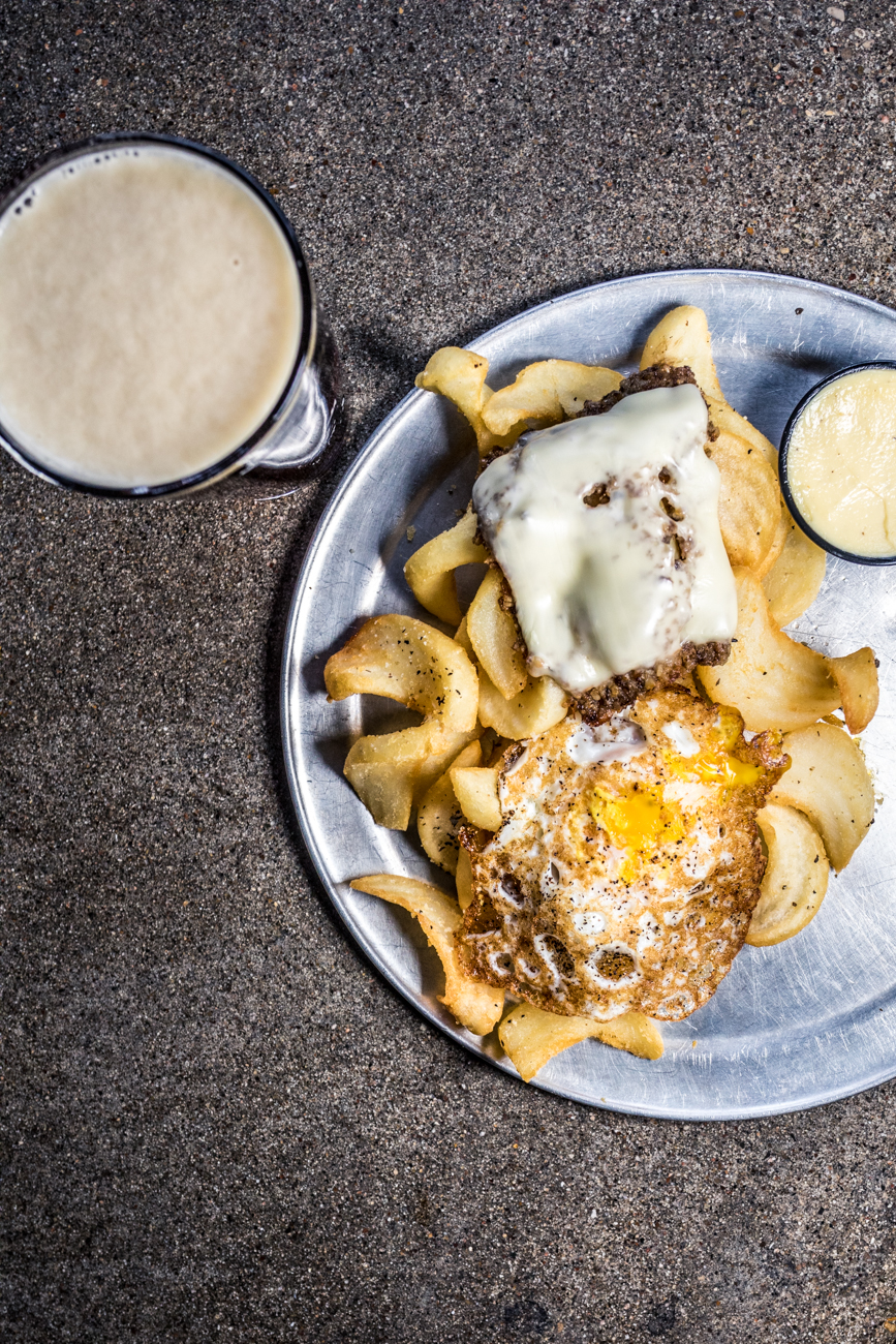 Cincy Fries with a slab of crispy goetta, american cheese, sriracha aioli, & an over easy egg paired with a red ale / Image: Catherine Viox // Published: 3.12.20