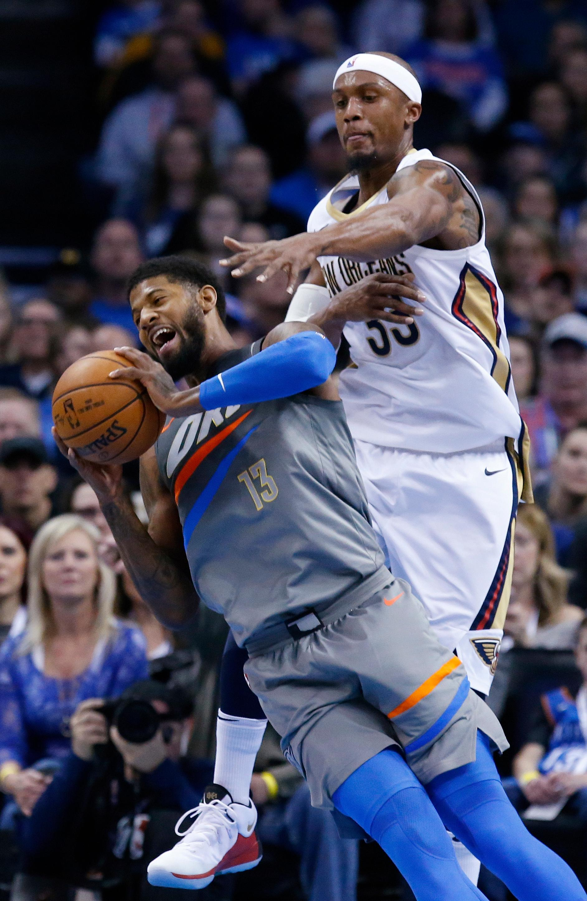 Oklahoma City Thunder forward Paul George (13) is fouled by New Orleans Pelicans forward Dante Cunningham (33) during the first half of an NBA basketball game in Oklahoma City, Friday, Feb. 2, 2018. (AP Photo/Sue Ogrocki)