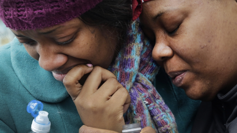 Alecia Thomas, left, is comforted by her friend, Shivon Dollar, after she lost her home following an explosion that leveled two apartment buildings in the East Harlem neighborhood of New York, Wednesday, March 12, 2014. (AP Photo/Mark Lennihan)