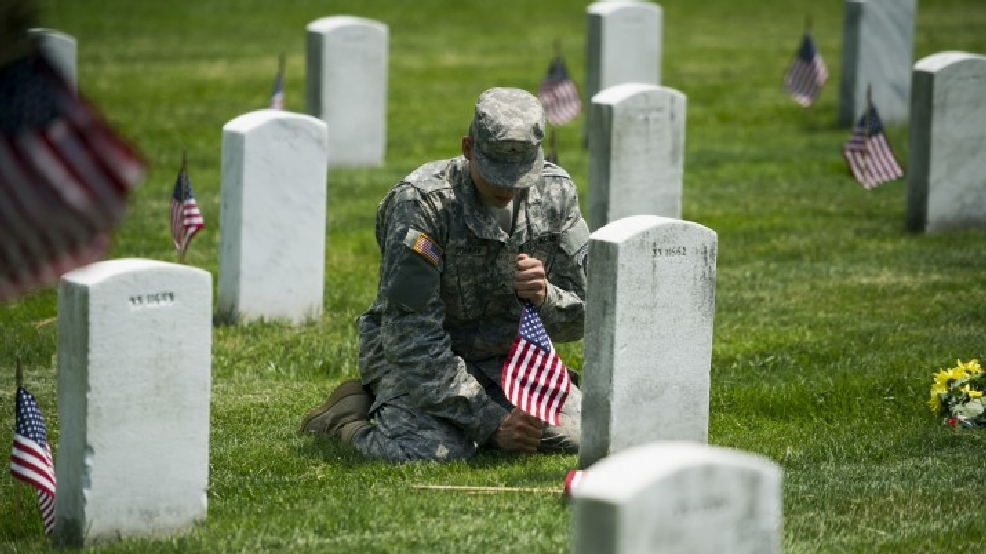 "Army Pvt. II Dylan Conway, 19, of Mason, Mich., of the 3rd U.S. Infantry Regiment, also known as The Old Guard, places flags at grave sites at Arlington National Cemetery in Arlington, Va., Thursday, May 22, 2014, as part of the annual ""Flags-In"" ceremony in preparation for Memorial Day. (AP Photo/Cliff Owen)"