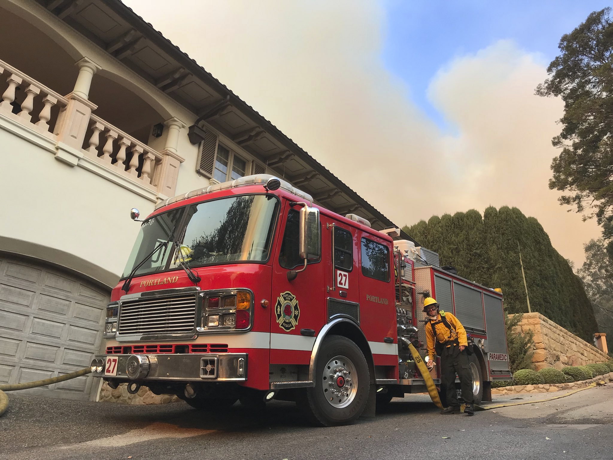 In this photo provided by the Santa Barbara County Fire Department, an engine company from Portland Ore., provides structure protection for a home near San Ysidro Road in Montecito, Calif., Saturday, Dec. 16, 2017. Santa Barbara County has issued new evacuation orders as a huge wildfire bears down on Montecito and other communities. The Office of Emergency Services announced the orders Saturday as Santa Ana winds pushed the fire close to the community.  Mike Eliason/Santa Barbara County Fire Department via AP)