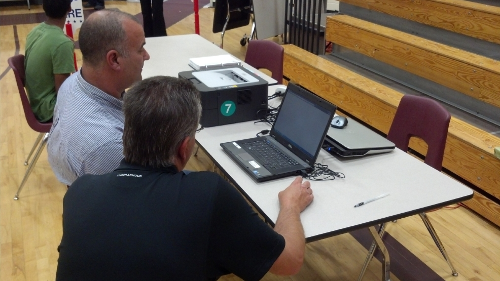 A voter at Fox Valley Lutheran High School in Appleton registers to vote on a laptop on Aug. 12, 2014. (WLUK/Andrew LaCombe)