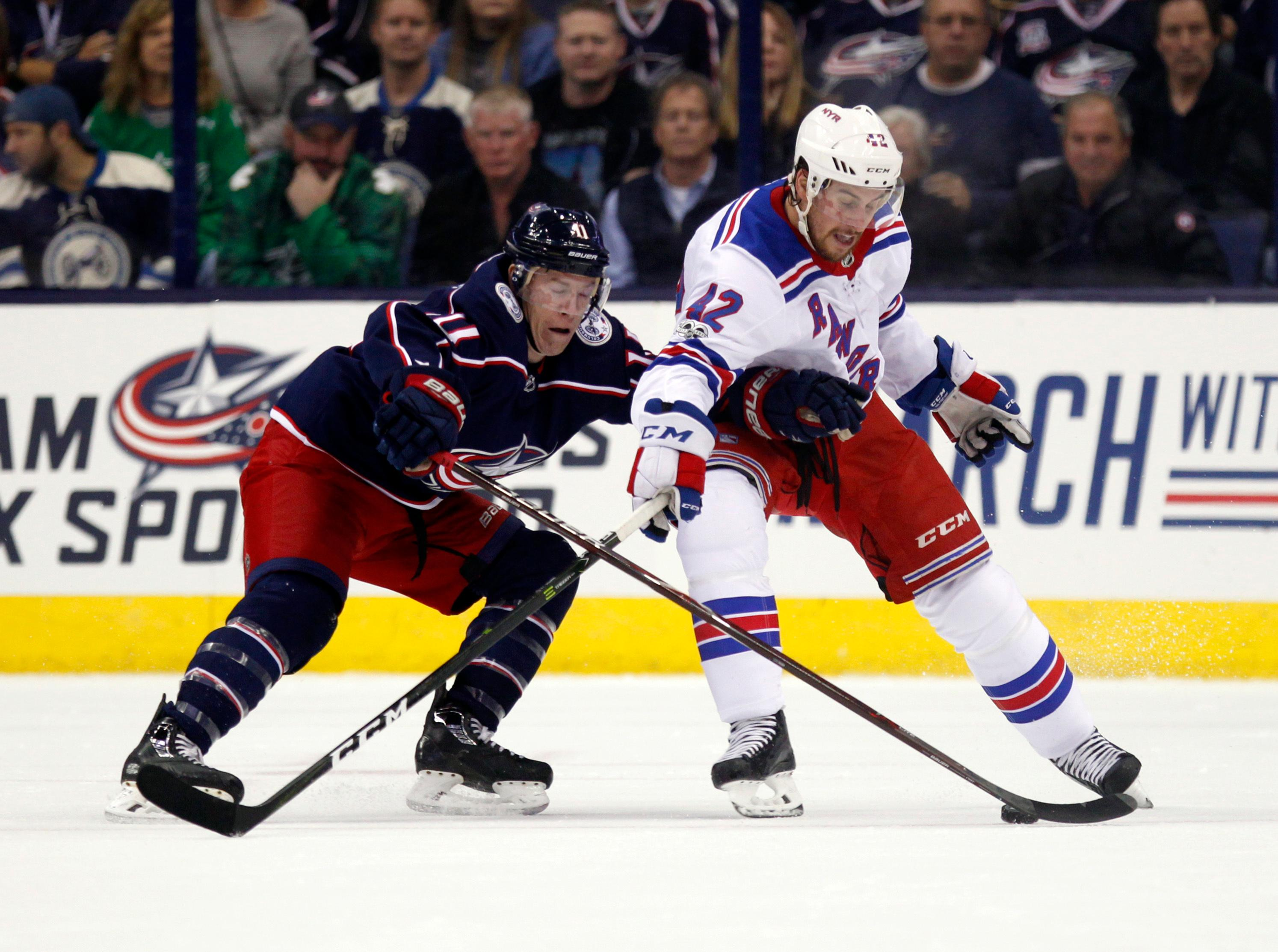 Columbus Blue Jackets forward Matt Calvert, left, tries to control the puck against New York Rangers defenseman Brendan Smith during the first period of an NHL hockey game in Columbus, Ohio, Friday, Oct. 13, 2017. (AP Photo/Paul Vernon)