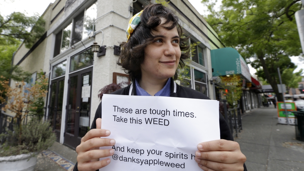 "Yeni Sleidi, known as the ""weed fairy,"" poses for a photo in Seattle's Capitol Hill neighborhood Wednesday, May 28, 2014, where this past weekend she posted 50 fliers with nuggets of marijuana taped to them. Sleidi, a 23-year-old who works in social media, has been visiting Seattle from New York where last year she did a similar posting, albeit anonymously. (AP Photo/Elaine Thompson)"