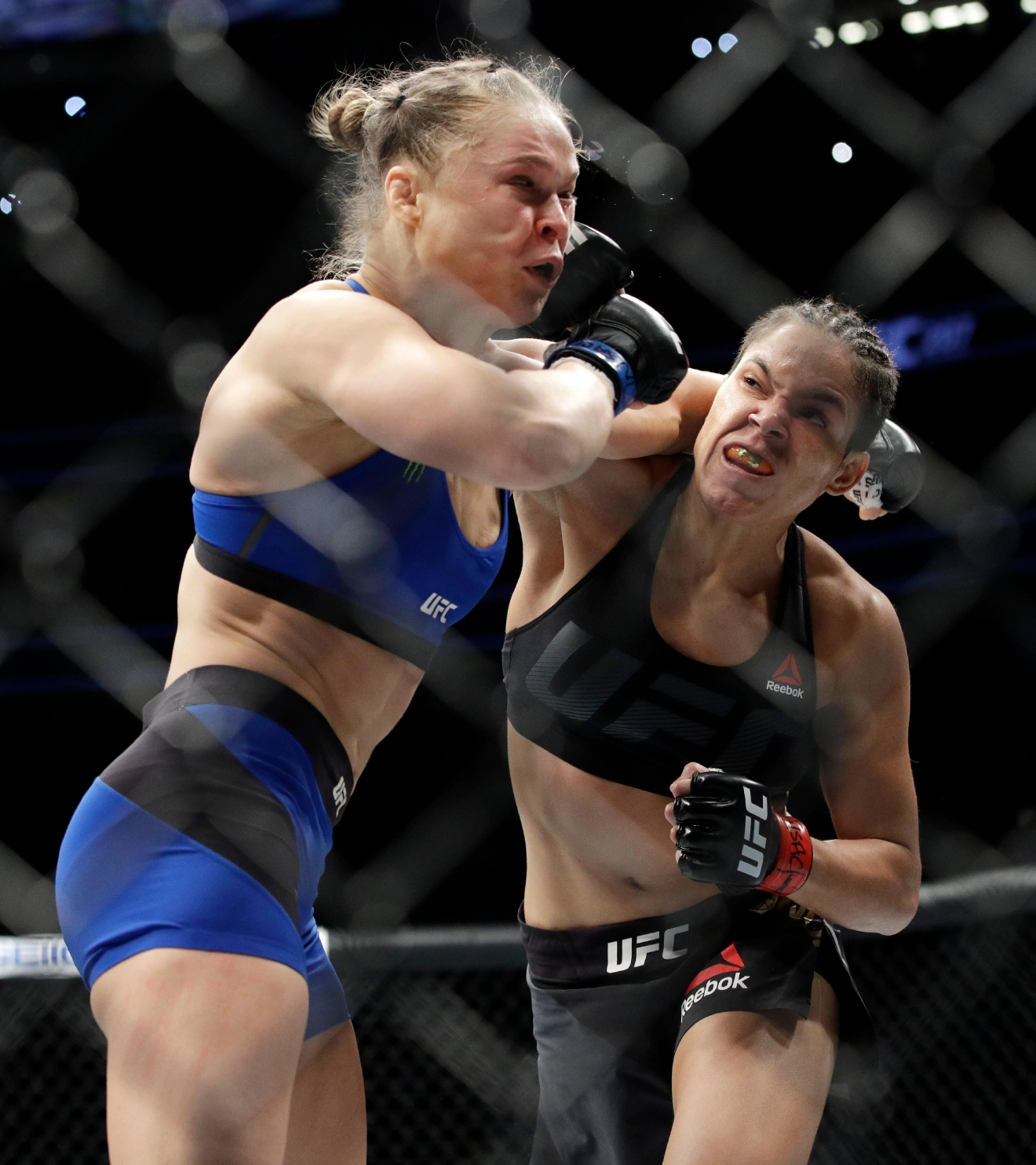 Amanda Nunes, right, connects with Ronda Rousey during the first round of their women's bantamweight championship mixed martial arts bout at UFC 207, Friday, Dec. 30, 2016, in Las Vegas. Nunes won the fight after it was stopped in the first round. (AP Photo/John Locher)