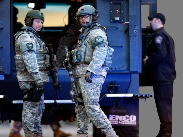 SWAT officers stand guard on the campus of Massachusetts General Hospital following explosions near finish line of the Boston Marathon.