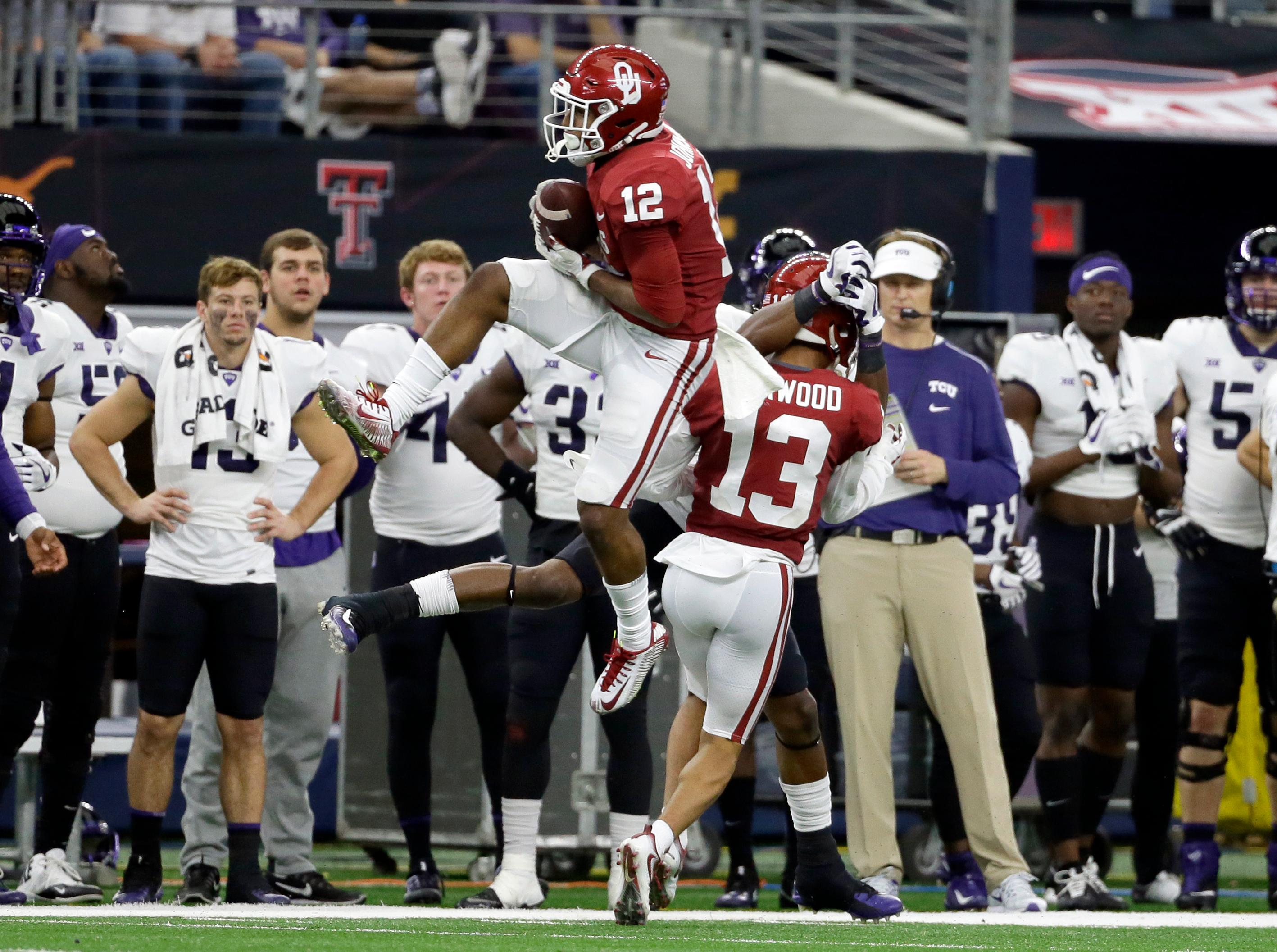 The TCU bench looks on as Oklahoma defensive back Will Johnson (12) intercepts a pass intended for TCU wide receiver John Diarse (9), rear, as cornerback Tre Norwood (13) helps on the play in the second half of the Big 12 Conference championship NCAA college football game, Saturday, Dec. 2, 2017, in Arlington, Texas. (AP Photo/Tony Gutierrez)