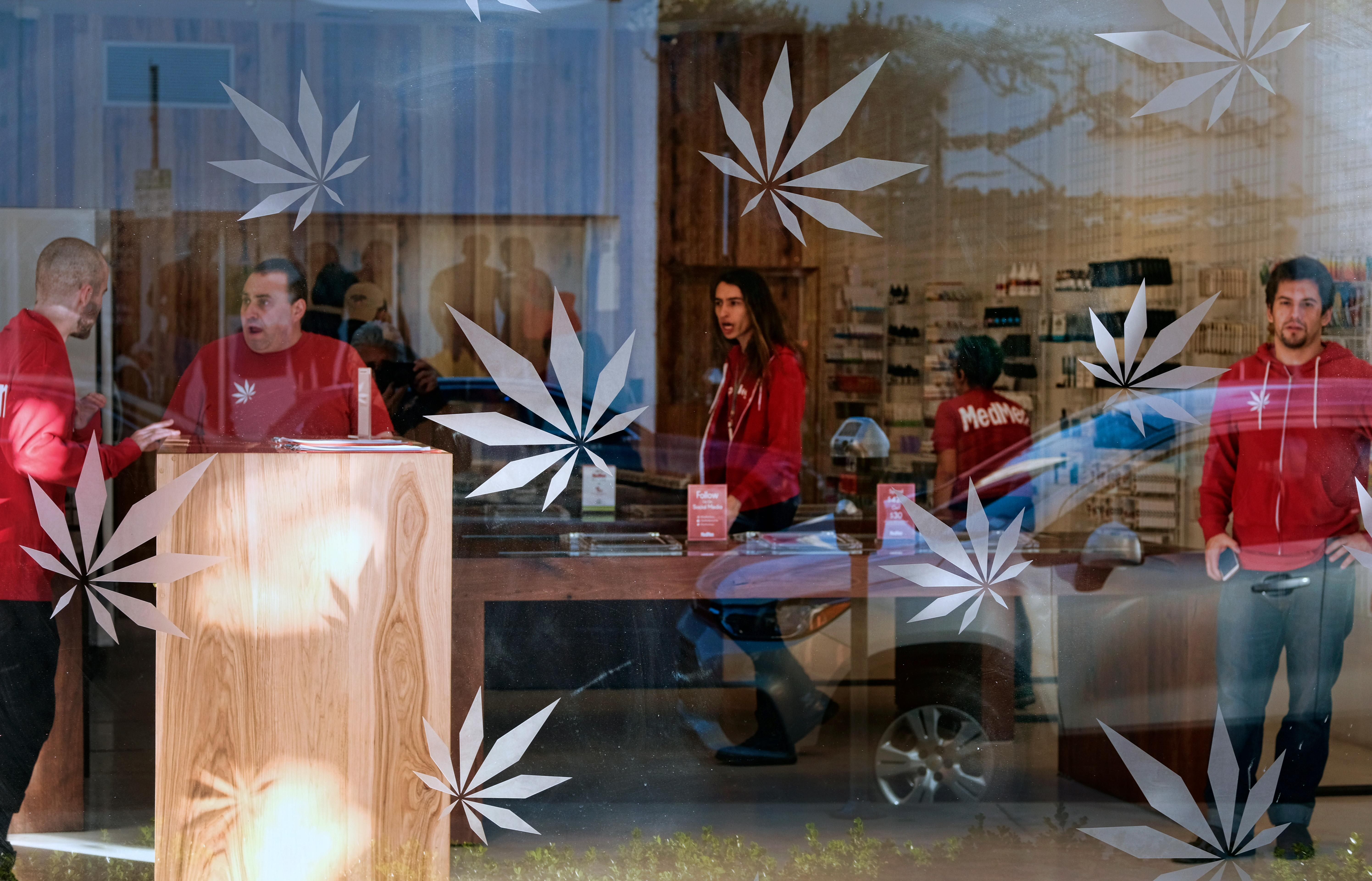 In this Thursday, Dec. 21, 2017 photo bud tenders wait for customers at MedMen a medical marijuana dispensary in Los Angeles . California kicks off recreational sales for adults on New Year's Day, but Los Angeles officials say dispensaries in the city won't be part of the celebration. The city announced Friday, Dec. 22, 2017, that it won't begin accepting applications to sell legal recreational pot until Jan. 3. It could take a month or more before those businesses are properly licensed with the city and state. (AP Photo/Richard Vogel)