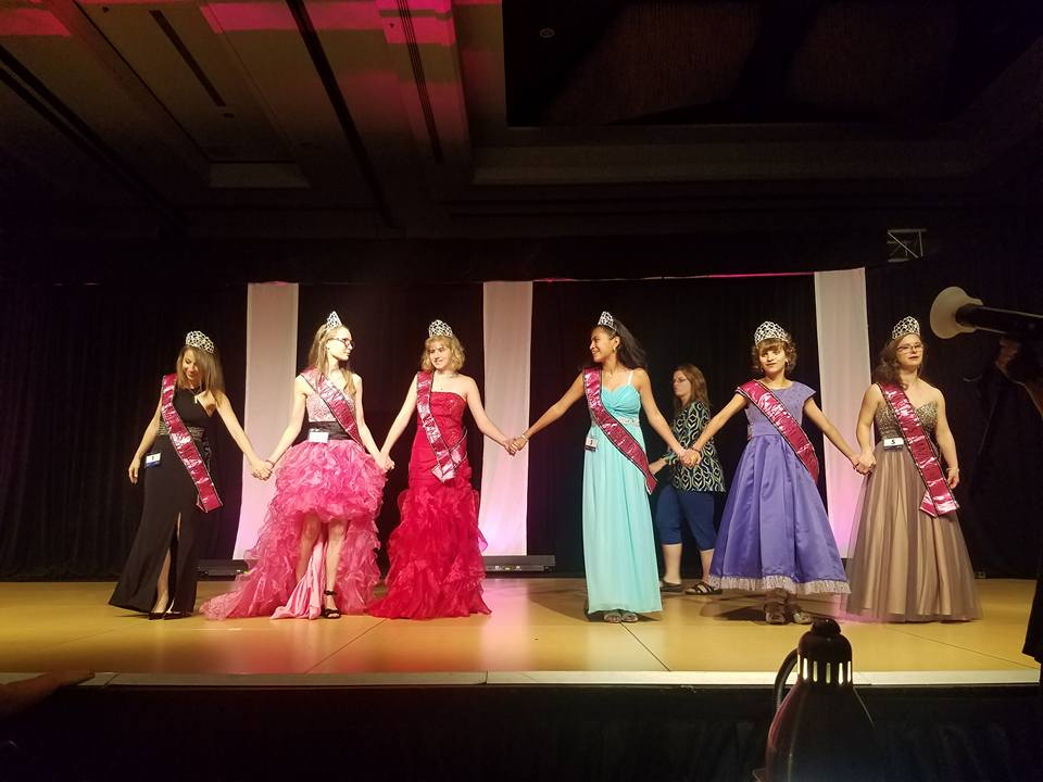 Jaymee Peterson (bright pink dress), Abigail Manery (purple dress) and Sarah Patterson (mauve dress) celebrate along with other contestants at the Miss Amazing Pageant in Chicago. Photo courtesy Ashlie Van Vorous