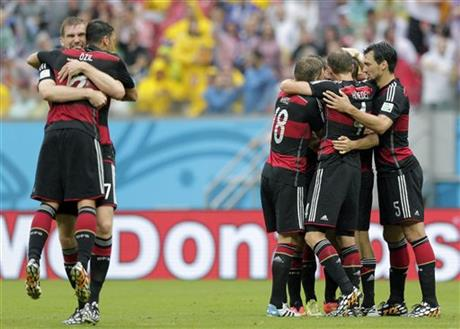 Germany's Per Mertesacker, left, hugs his teammate Mesut Ozil after Germany's Thomas Mueller scored the opening goal during the group G World Cup soccer match between the USA and Germany at the Arena Pernambuco in Recife, Brazil, Thursday, June 26, 2014.