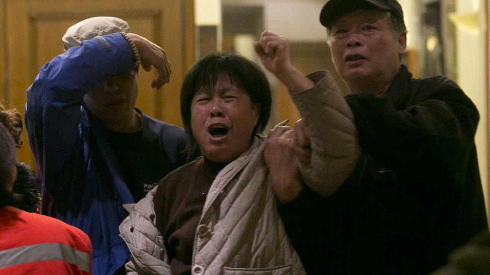 A relative of one of the Chinese passengers aboard the Malaysia Airlines, MH370 grieves after being told of the latest news in Beijing, China, Monday, March 24, 2014. (AP Photo/Ng Han Guan)