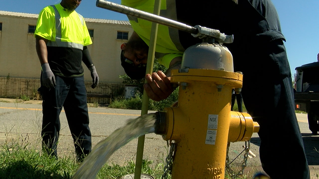 Workers with the Macon Water Authority service a fire hydrant in Bibb County. Eric Mock/WGXA