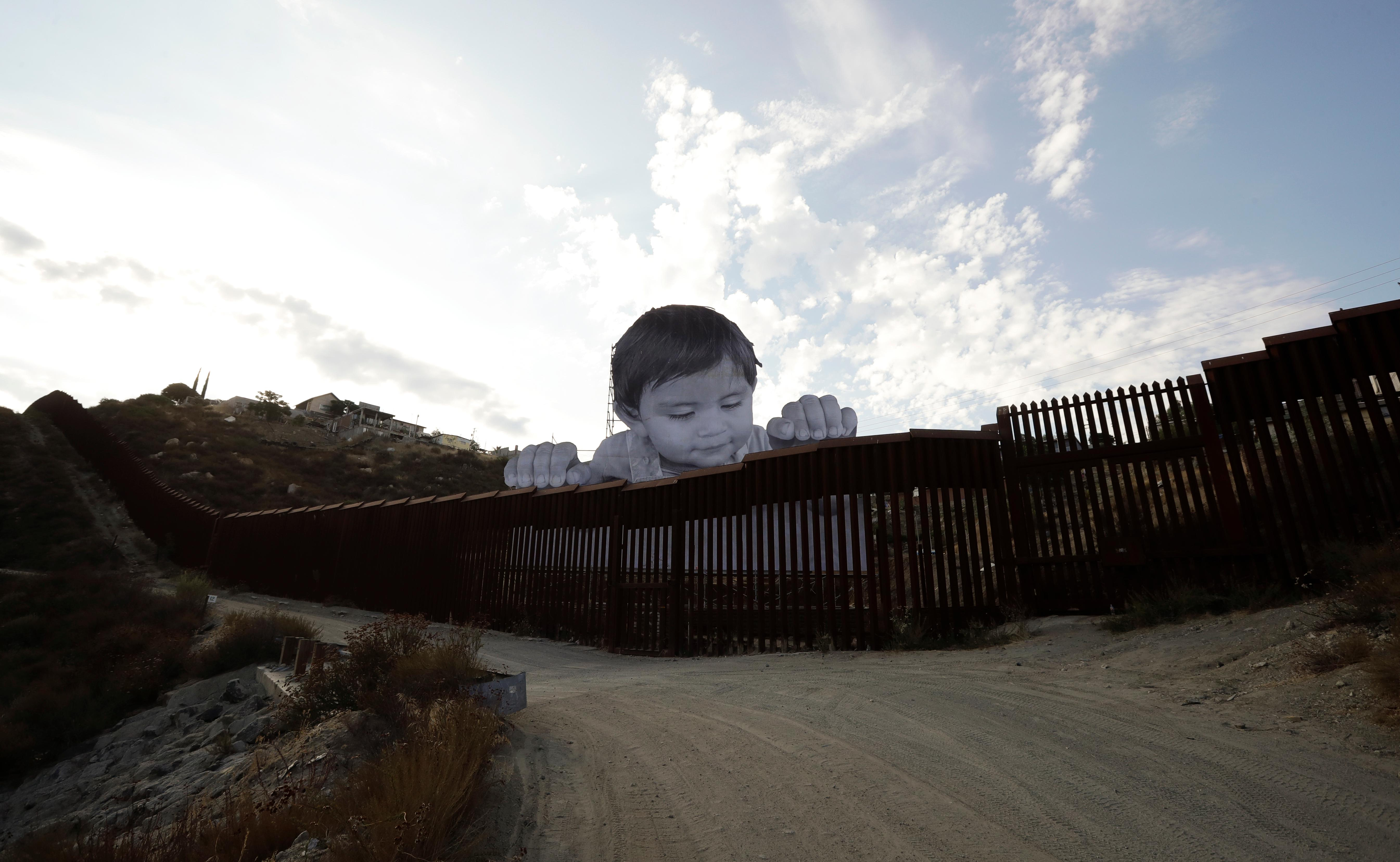 A mural in Tecate, Mexico, sits just beyond a border structure Friday, Sept. 8, 2017, seen from Tecate, Calif. A French artist aiming to prompt discussions about immigration erected a 65-foot-tall cut-out photo of a Mexican boy, pasting it to scaffolding built in Mexico. The image overlooks a section of wall on the California border and will be there for a month. (AP Photo/Gregory Bull)