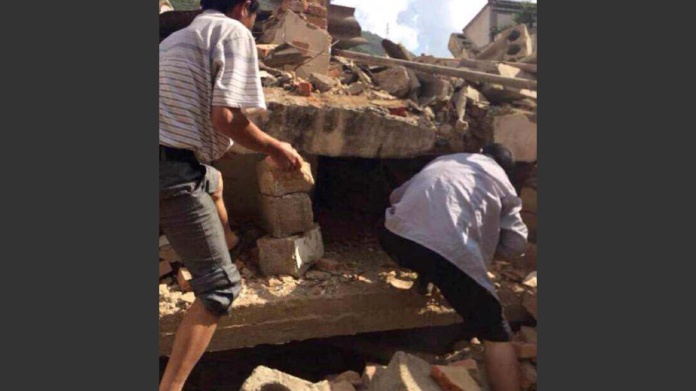 In this photo taken by cellphone and released by China's Xinhua News Agency, men at rubbles of buildings look for survivors after an earthquake in Ludian County of Zhaotong City in southwest China's Yunnan Province Sunday, Aug. 3, 2014. A strong earthquake rattled southwest China on Sunday, knocking out communication and power lines and causing people to rush out of buildings, but there were no immediate reports of injuries. (AP Photo/Xinhua/Hu Chao)