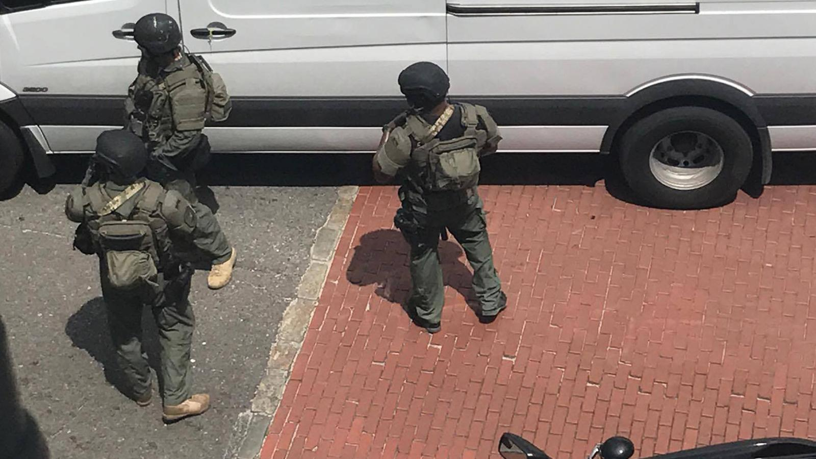 Armored officers stand ready outside a van on the street near the Virginia's on King restaurant. (Provided/Robbie Kimbrough)