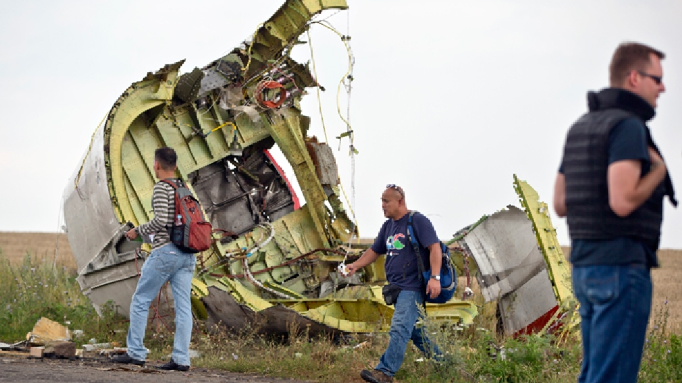 Malaysian air crash investigators walk by wreckage at the crash site of Malaysia Airlines Flight 17 near the village of Hrabove, eastern Ukraine, Tuesday, July 22, 2014. A team of Malaysian investigators visited the site along with members of the OSCE mission in Ukraine for the first time since the air crash last week. (AP Photo/Vadim Ghirda)