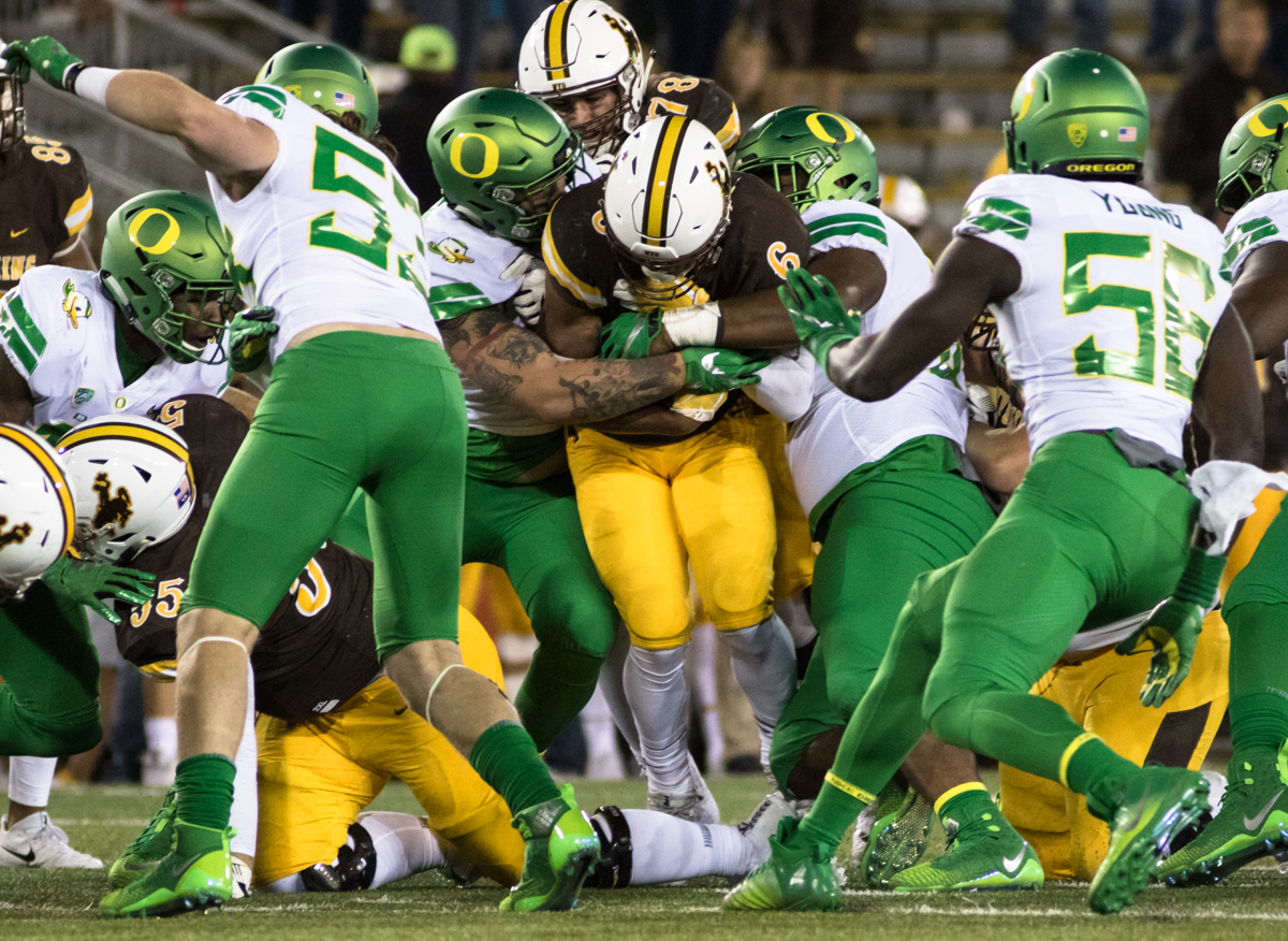 The Oregon line gang-tackles Wyoming running back Trey Woods (#6). The Oregon Ducks recorded their first road win under head coach Willie Taggart with their 49-13 victory over the Wyoming Cowboys on a cold night at War Memorial Stadium in Laramie, Wyoming.  Photo by Austin Hicks, Oregon News Lab
