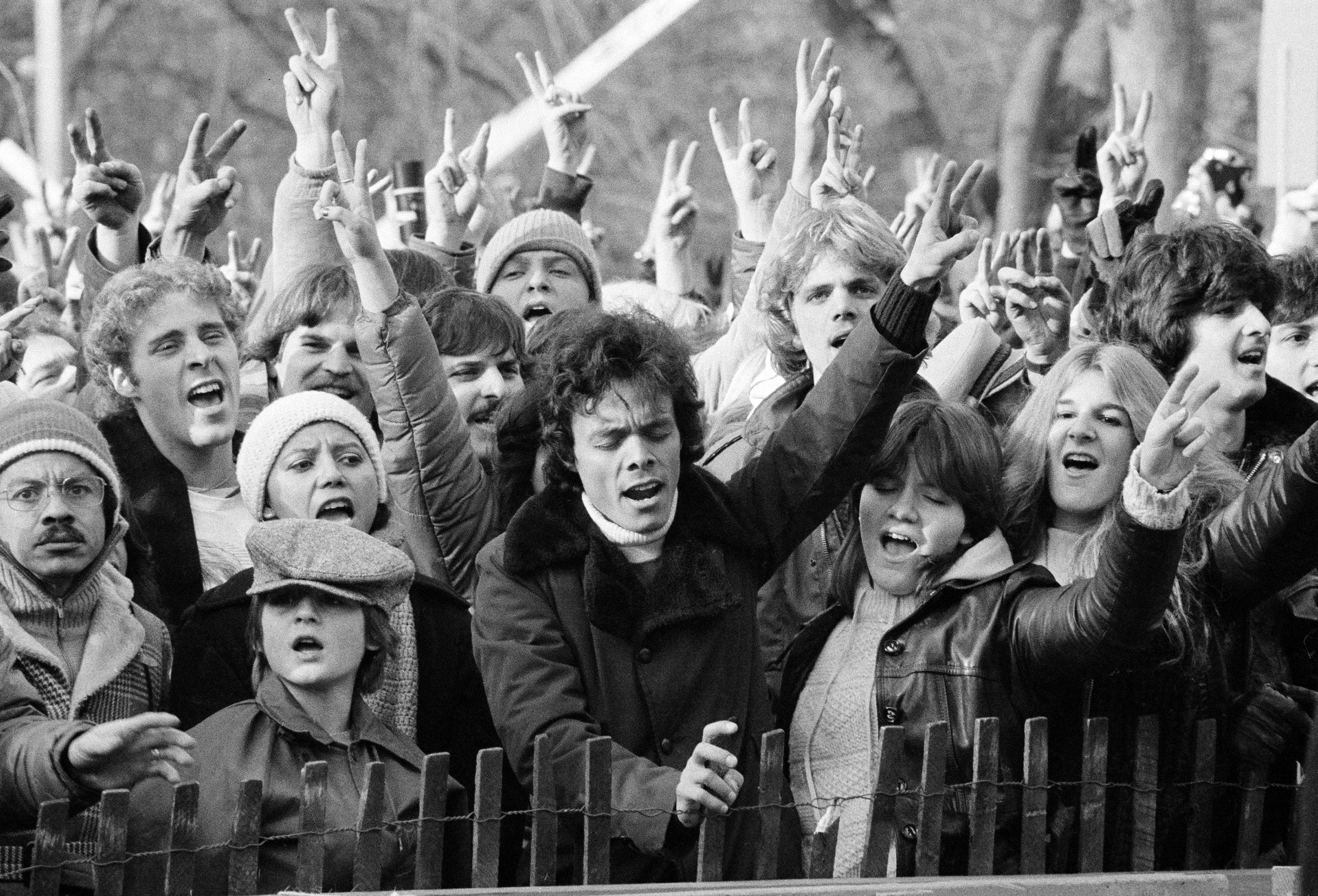 "FILE - In this Dec. 14, 1980, file photo, people participating in tribute to the slain musician John Lennon wave the peace sign and sing ""Give Peace A Chance"" at New York's Central Park. Thirty-five years ago on Dec. 8, Mark David Chapman shot and killed Lennon, a former Beatles member. (AP Photo/Carlos Rene Perez, File)"