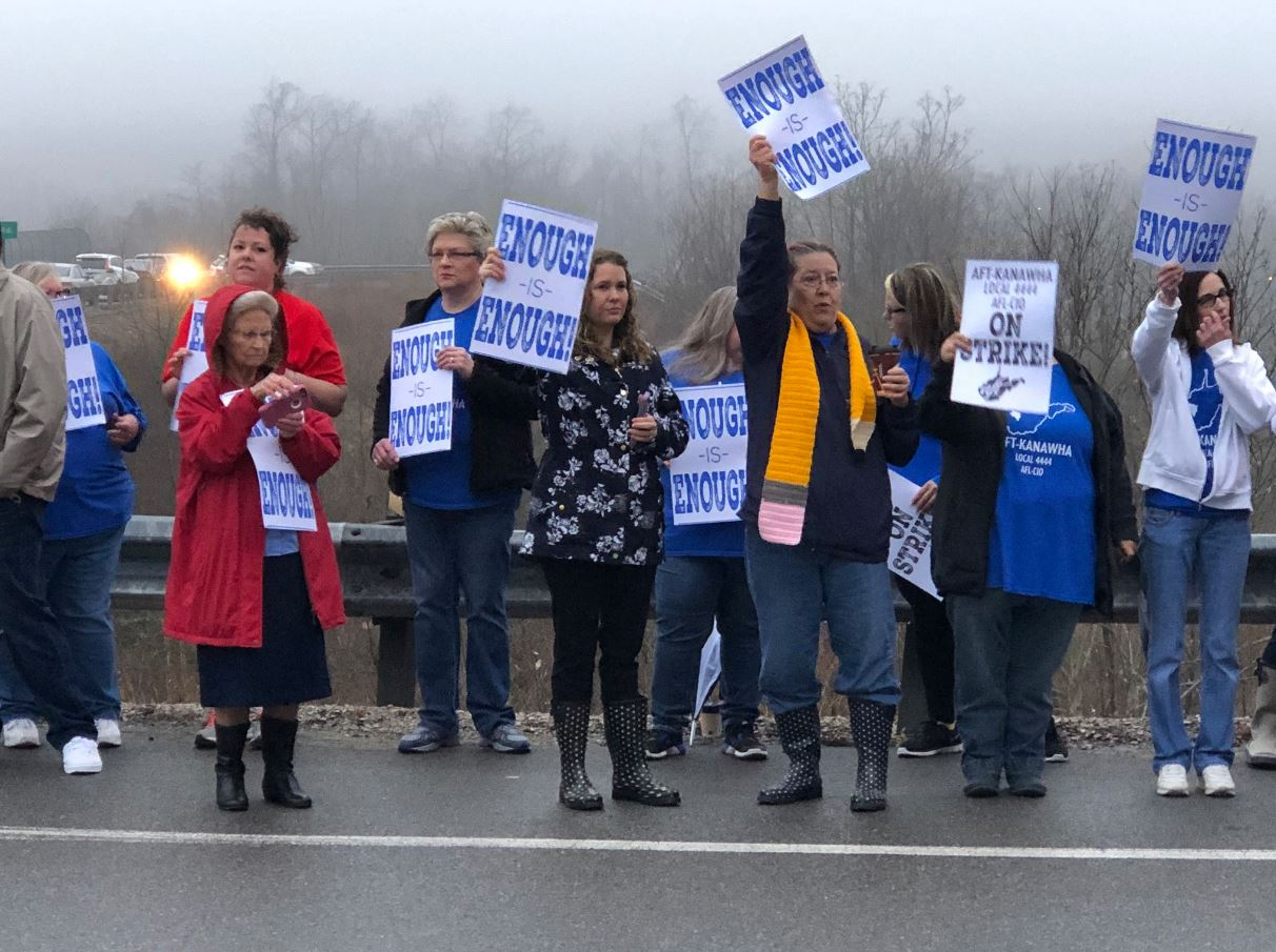 Teachers and school service personnel hold signs that read &quot;enough is enough&quot; and &quot;you can't put students first if you put teachers last.&quot; (WCHS/WVAH)<p></p>