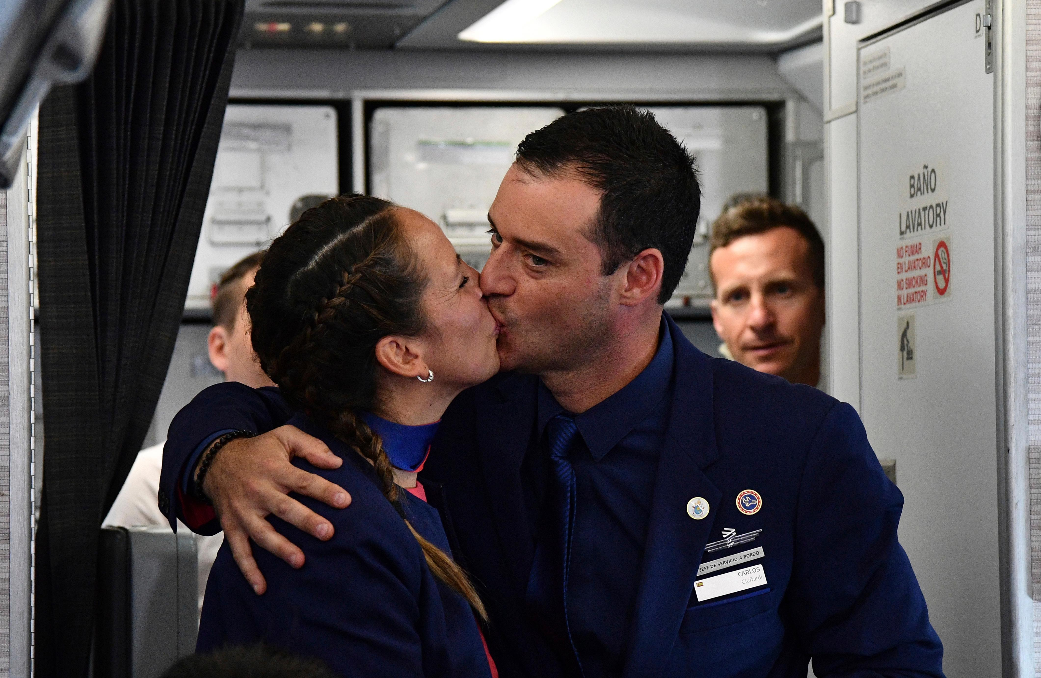Crew members Paula Podest and Carlos Ciufffardi kiss before journalists after being married by Pope Francis during the flight between Santiago and the northern city of Iquique, Chile, Thursday, Jan. 18, 2018. Pope Francis celebrated the first-ever airborne papal wedding, marrying these two flight attendants from Chile's flagship airline during the flight. The couple had been married civilly in 2010, however, they said they couldn't follow-up with a church ceremony because of the 2010 earthquake that hit Chile. (Vincenzo Pinto, POOL via AP)