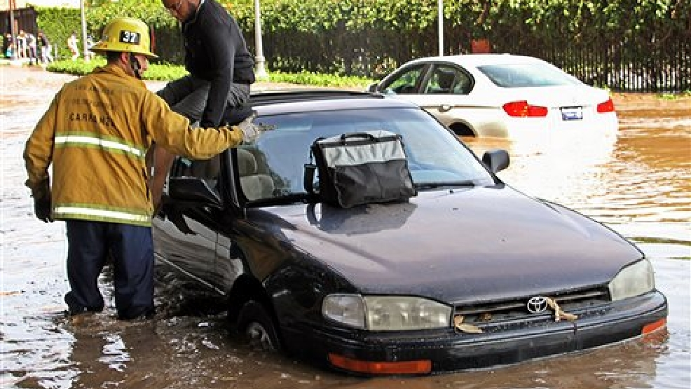 A Los Angeles firefighter helps a driver whose car became stranded on Sunset Boulevard after a 30-inch water main broke and sent water flooding down Sunset and onto the UCLA campus in the Westwood section of Los Angeles Tuesday, July 29, 2014. (AP Photo/Steve Gentry)
