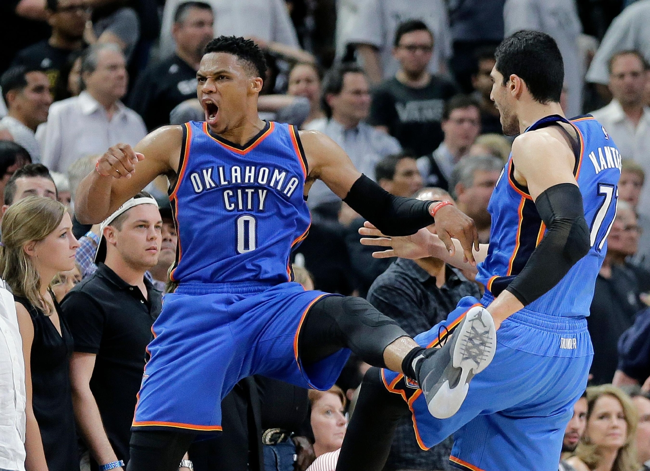 Oklahoma City Thunder guard Russell Westbrook (0) celebrates with teammate Enes Kanter (11) after he scored against the San Antonio Spurs during the final seconds of Game 5 of a second-round NBA basketball playoff series, Tuesday, May 10, 2016, in San Antonio. Oklahoma City won 95-91. (AP Photo/Eric Gay)