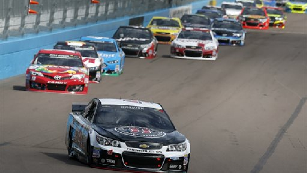 Kevin Harvick leads a group of cars into Turn 1 during the NASCAR Sprint Cup Series auto race Sunday, March 2, 2014, in Avondale, Ariz. (AP Photo/Ross D. Franklin)