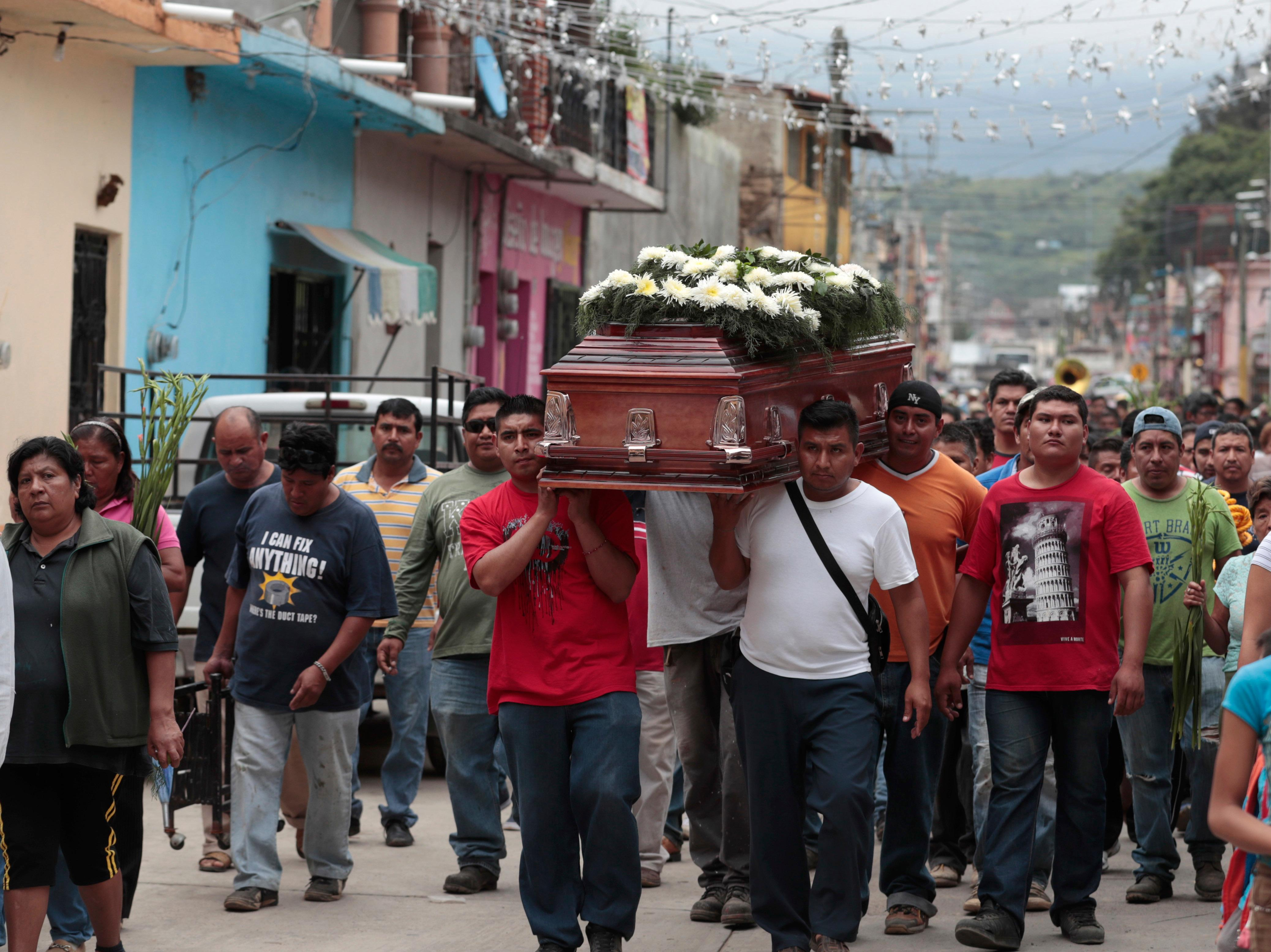 Locals carry the casket of a woman who died in Tuesday's earthquake, in Tlayacapan, Morelos state, Mexico, Wednesday, Sept. 20, 2017. People by the millions rushed from homes and offices across central Mexico after a 7.1 earthquake, sometimes watching as buildings they had just fled fell behind them with an eruption of dust and debris. (AP Photo/Eduardo Verdugo)
