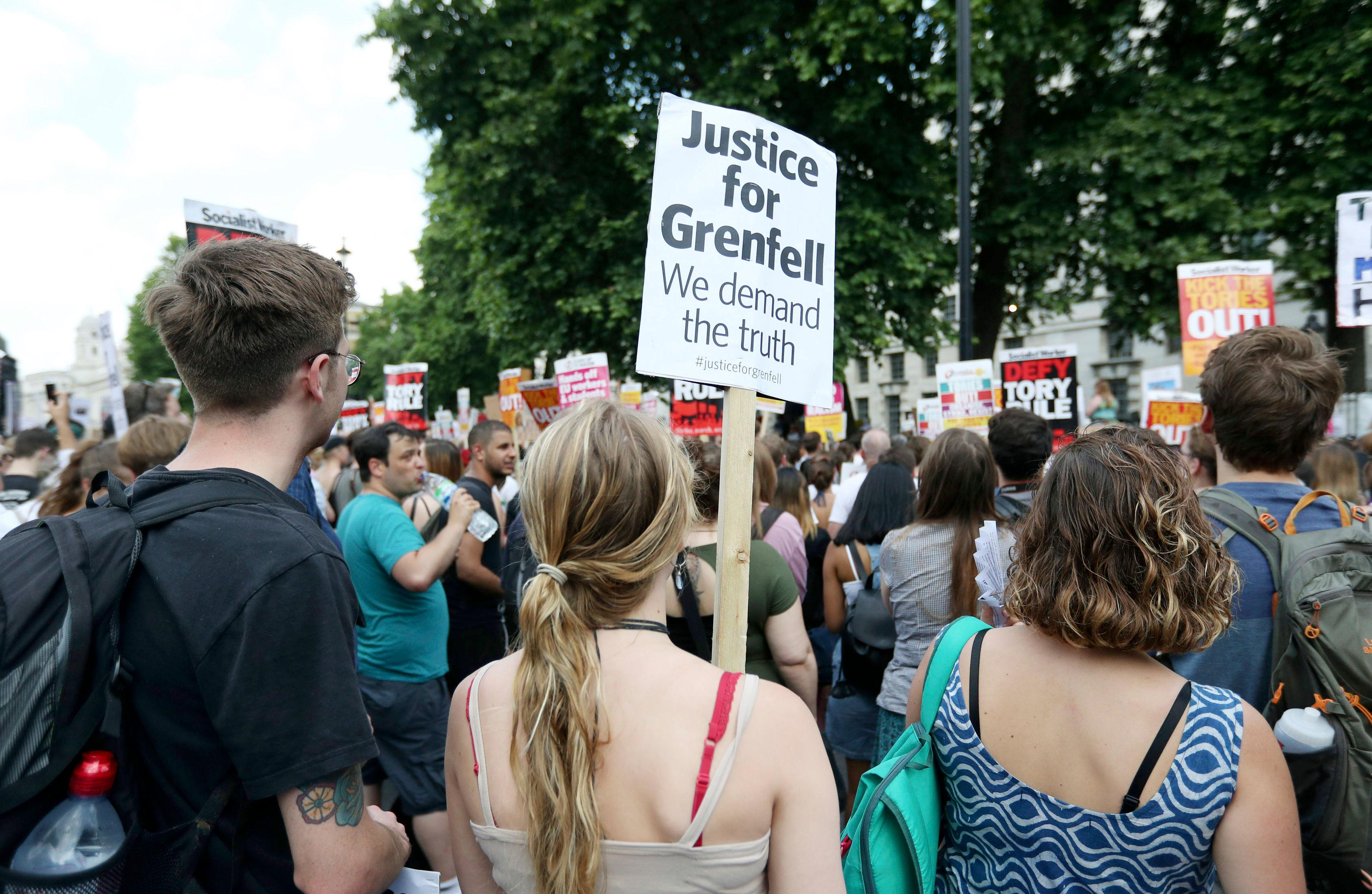 People gather in Whitehall, to protest after the fire at Grenfell Tower which engulfed the 24 storey building on Wednesday, in London, Saturday June 17, 2017. More than 3 million pounds ($3.8 million) has been raised for victims of the London high-rise fire that has killed at least 30 people and left dozens homeless. (?Jonathan Brady/PA via AP)