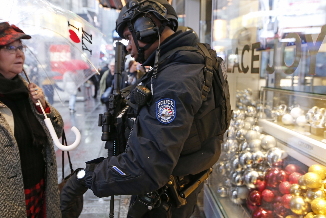 A woman stops to ask directions from a heavily armed counterterrorism officer, Thursday, Dec. 29, 2016, in Times Square in New York. Police say they are up to the task of protecting the huge crowds that are expected to gather in and around Times Square for New York City's massive New Year's Eve celebration. (AP Photo/Kathy Willens)