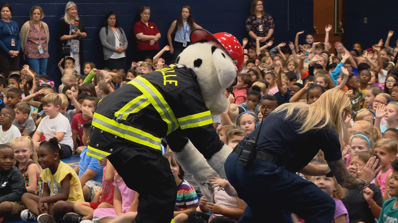 Firefighters and Estes Elementary students kick off the Firefighters for Literacy program. (Photo credit: WLOS staff)