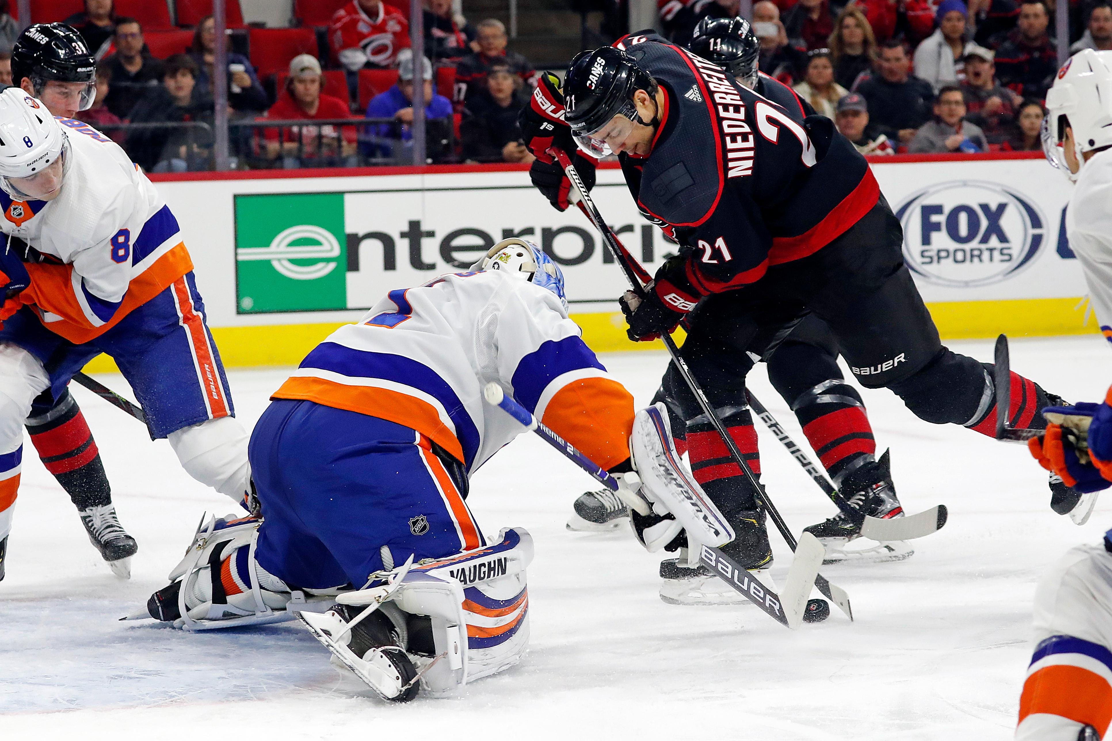 Carolina Hurricanes' Nino Niederreiter (21), of Switzerland, tries to control the puck in front of New York Islanders goaltender Thomas Greiss (1), of Germany, during the first period of an NHL hockey game in Raleigh, N.C., Sunday, Jan. 19, 2020. (AP Photo/Karl B DeBlaker)