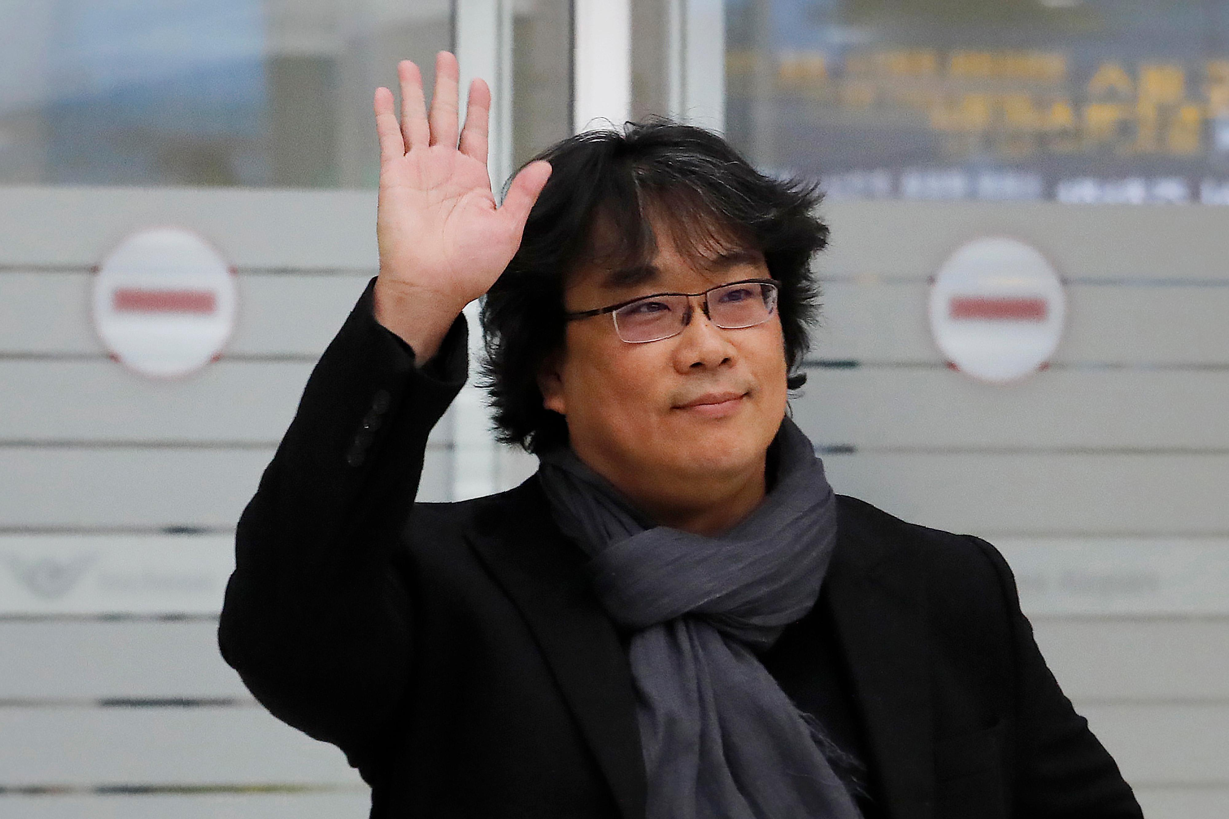 "South Korean director Bong Joon-ho waves upon his arrival at the Incheon International Airport in Incheon, South Korea, Sunday, Feb. 16, 2020. South Koreans are reveling in writer-director Bong's dark comic thriller, ""Parasite,"" which won this year's Academy Awards for best film and best international feature. The movie itself, however, doesn't put the country in a particularly positive light. (AP Photo/Ahn Young-joon)"