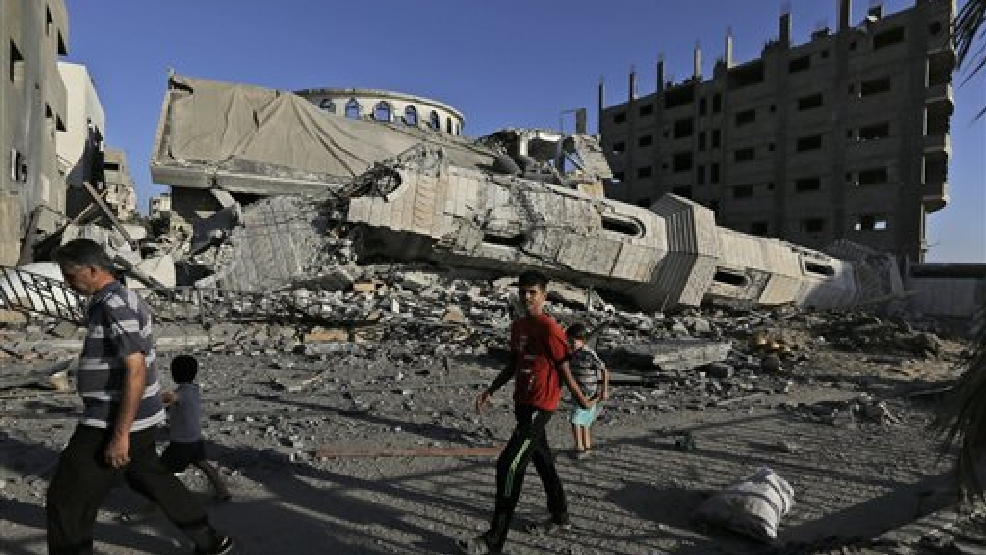 Palestinians walk by the rubble of the toppled minaret of the Abu Jihad Al Wazer mosque, destroyed by an Israeli strike during the war, in Gaza City, Monday, Aug. 11, 2014. (AP Photo/Lefteris Pitarakis)