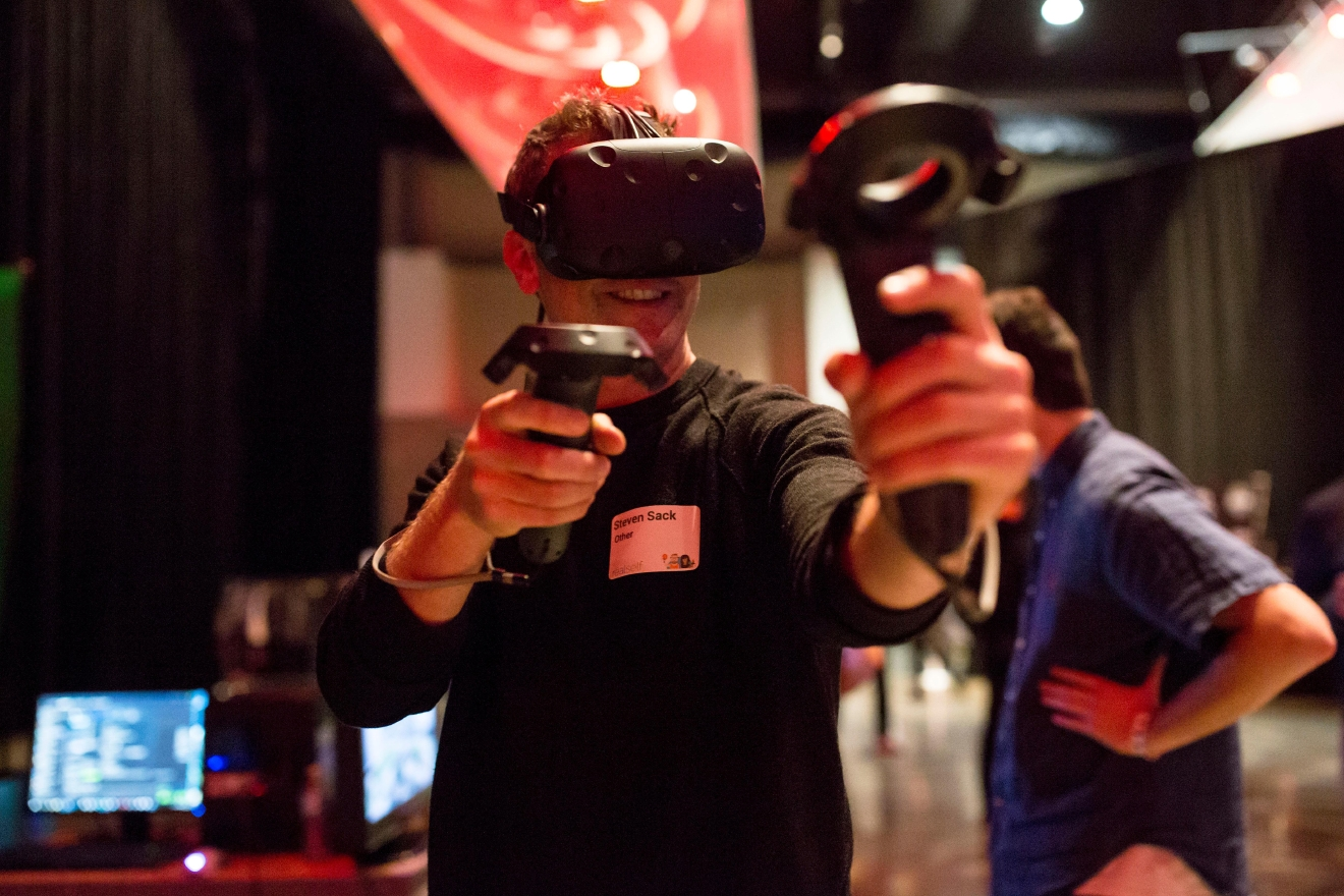 Steven Sack takes aim as he shoots a bow and arrow in virtual reality at the 6th annual Geekwire Bash at the CenturyLink Event Center. (Sy Bean / Seattle Refined)