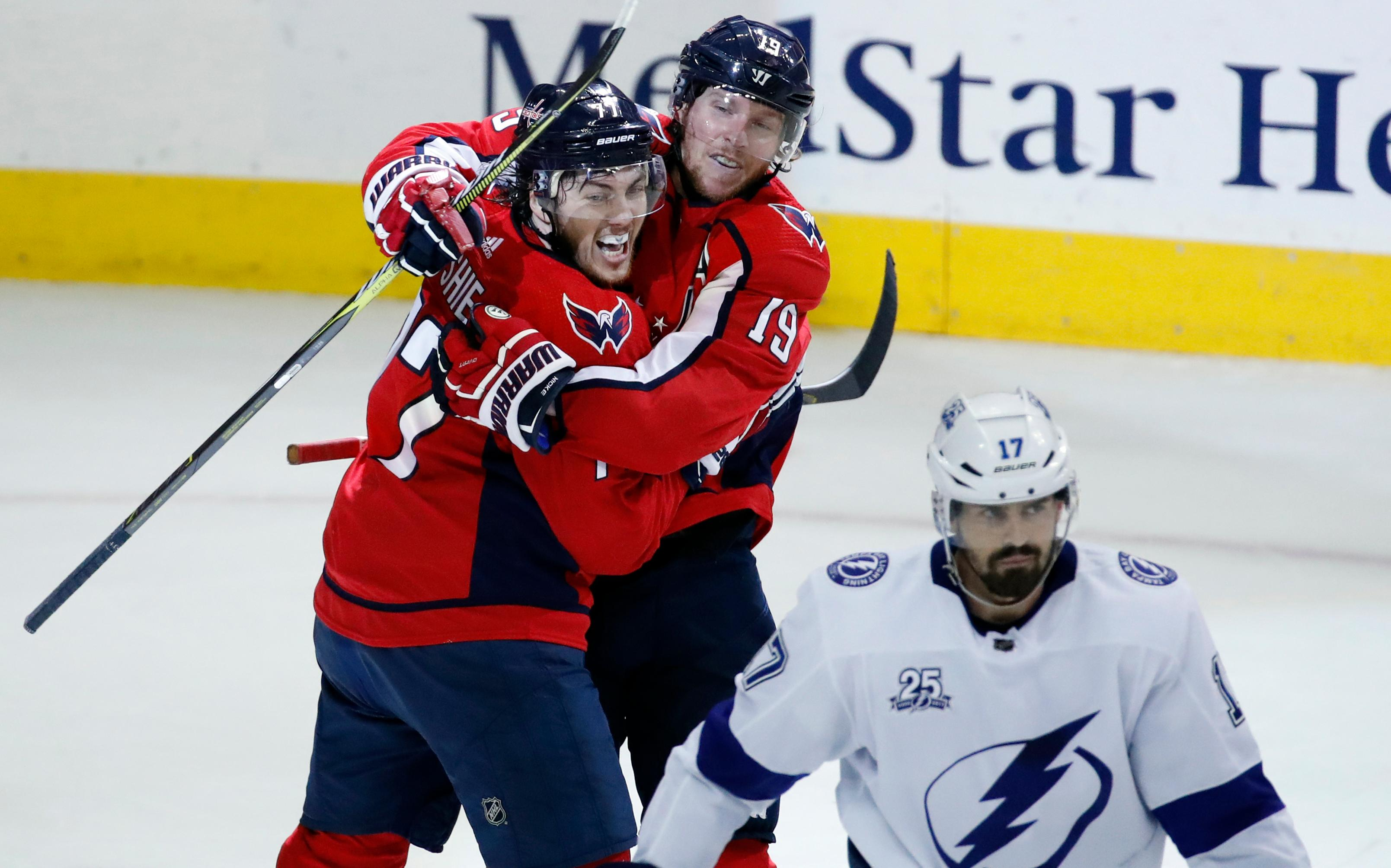 Washington Capitals right wing T.J. Oshie, left, and center Nicklas Backstrom, from Sweden, celebrate a goal by Oshie with Tampa Bay Lightning left wing Alex Killorn (17) nearby during the second period of Game 6 of the NHL Eastern Conference finals hockey playoff series, Monday, May 21, 2018, in Washington. (AP Photo/Alex Brandon)