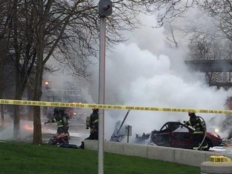 In this photo provided by KOMO-TV, emergency personnel respond to the scene of a helicopter crash outside the KOMO-TV studios near the space needle in Seattle on Tuesday, March 18, 2014.