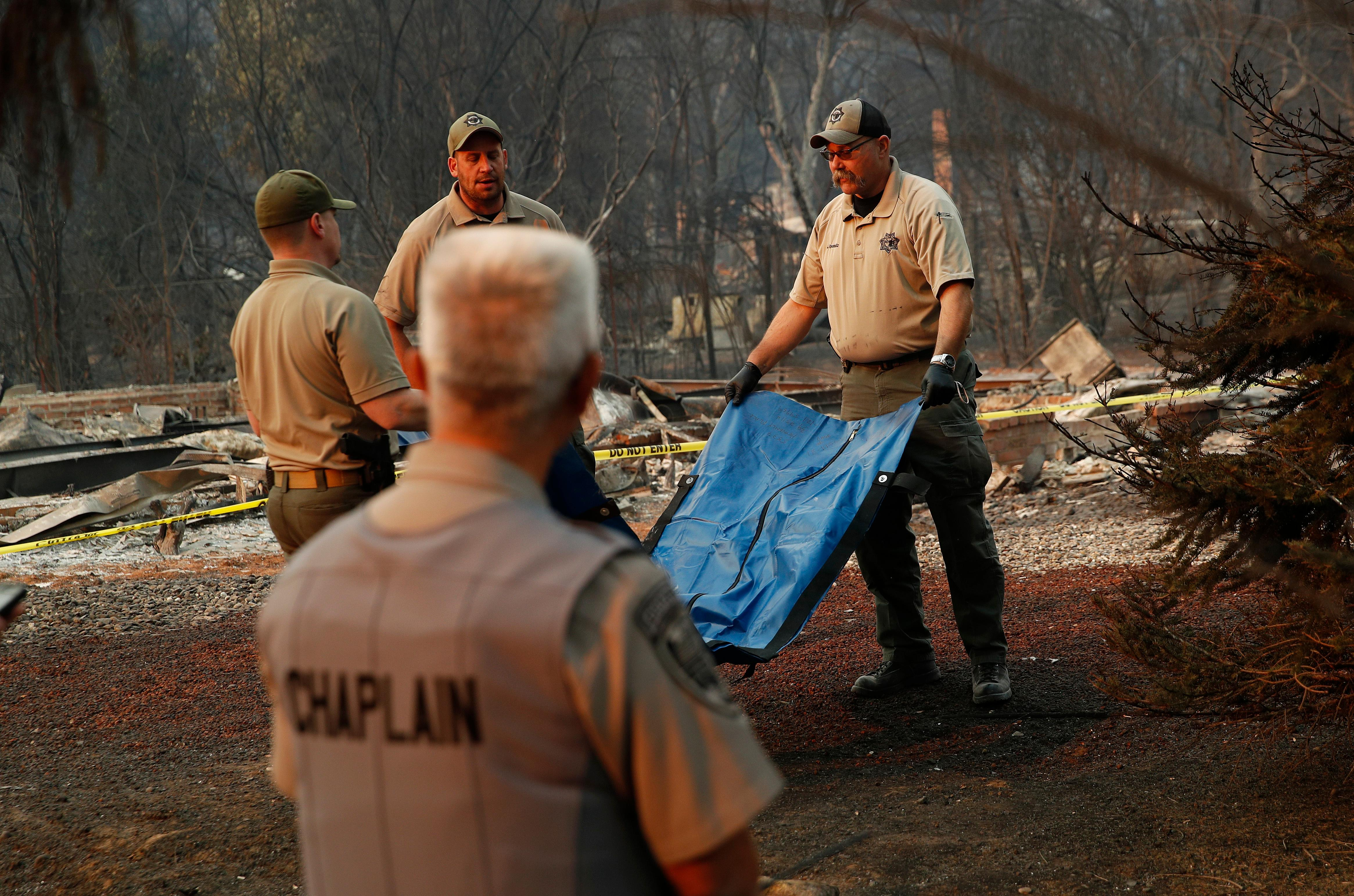Deputy Coroner Justin Sponhaltz, right, of the Mariposa County Sheriff's Office, carries a bag with human remains found at a burned out home at the Camp Fire, Sunday, Nov. 11, 2018, in Paradise, Calif. (AP Photo/John Locher)