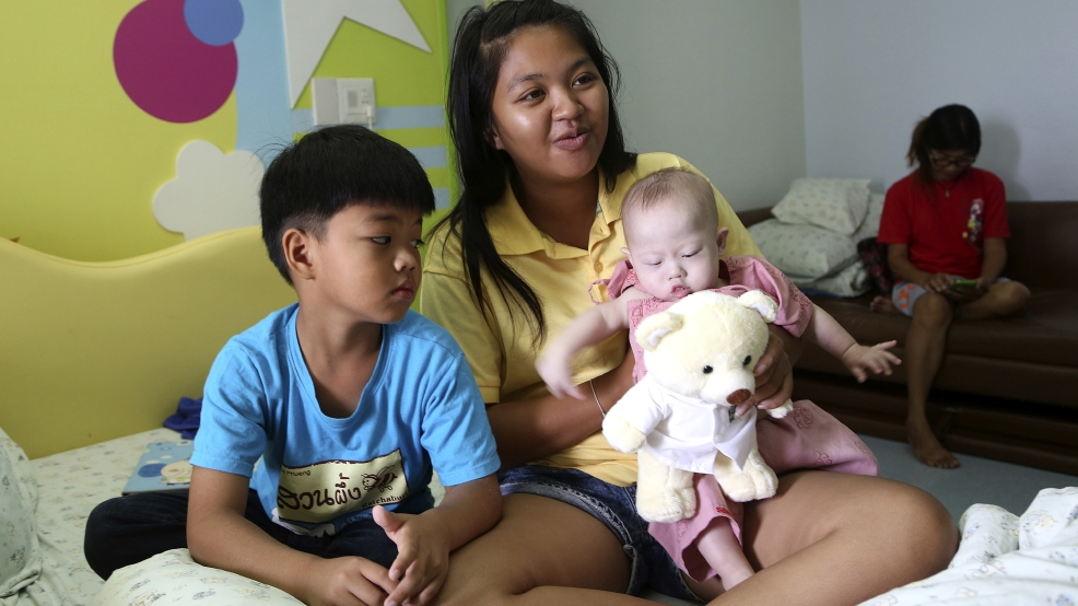 Pattaramon Chanbua, 21, poses with her children Game, 7, left, and baby boy Gammy at a hospital in Chonburi province, southeastern Thailand Sunday, Aug. 3, 2014. The Australian government is consulting Thai authorities after news emerged that Gammy, a baby with Down Syndrome was abandoned with Chanbua, his surrogate mother, in Thailand by his Australian parents, according to local media. (AP Photo/Apichart Weerawong)