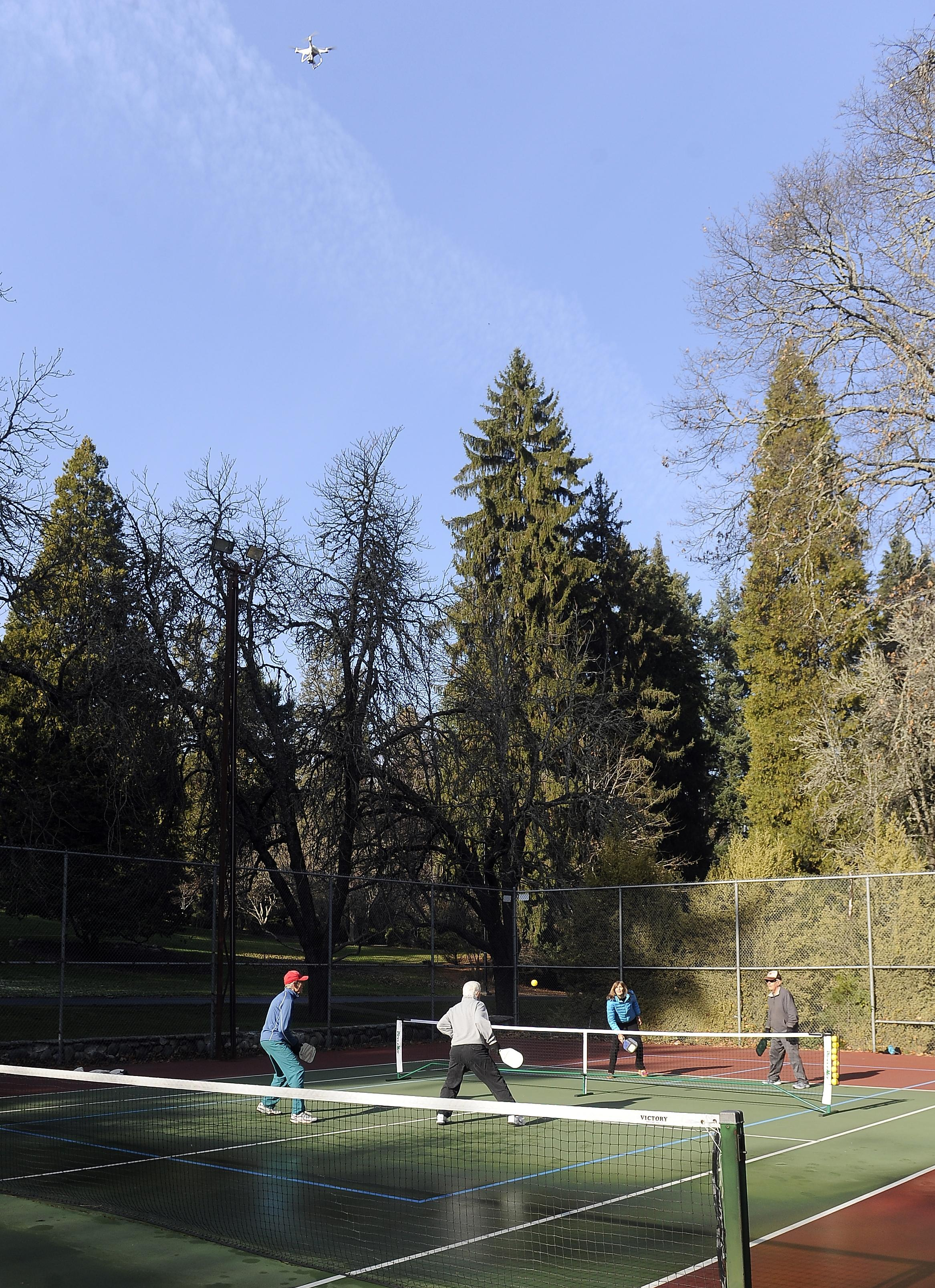 From left, Dane Roubos, Stewart Grey, Kim Marie Murphy and Bob Valine play a game of pickleball with a drone flying over the match in Lithia Park earlier this month. [Mail Tribune / Andy Atkinson]