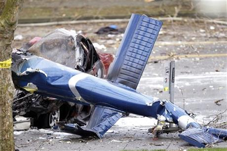 The wreckage of a news helicopter sits on a city street after crashing Tuesday, March 18, 2014, in Seattle.