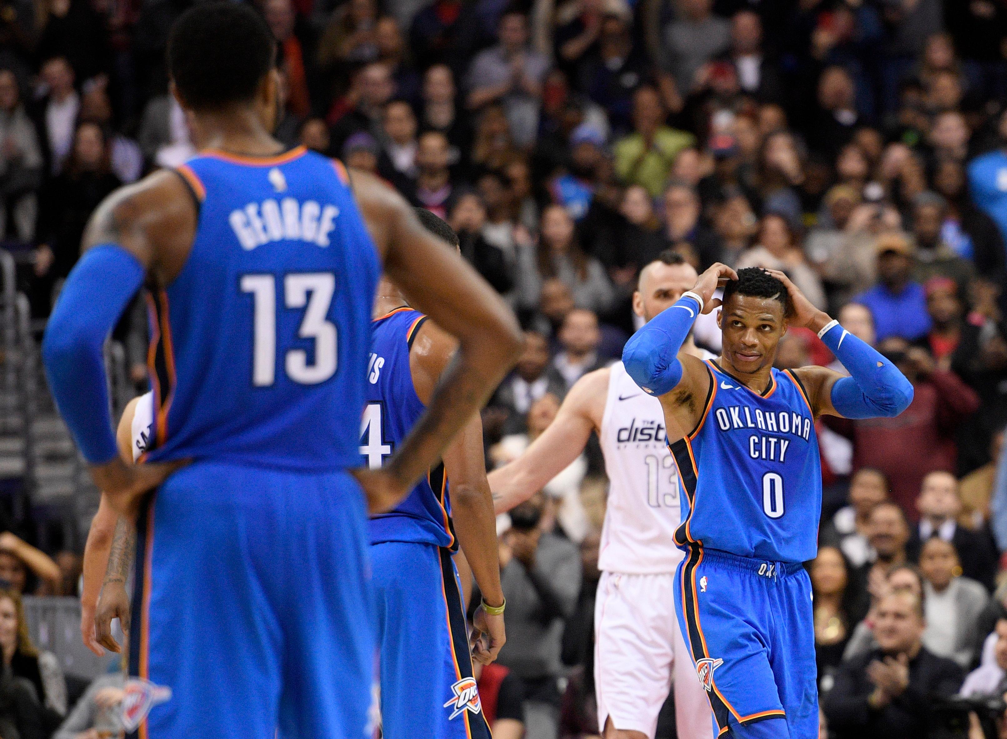 Oklahoma City Thunder guard Russell Westbrook (0) reacts in front of Washington Wizards center Marcin Gortat, back, during the second half of an NBA basketball game Tuesday, Jan. 30, 2018, in Washington. Also seen is Thunder forward Paul George (13). The Wizards won 102-96. (AP Photo/Nick Wass)